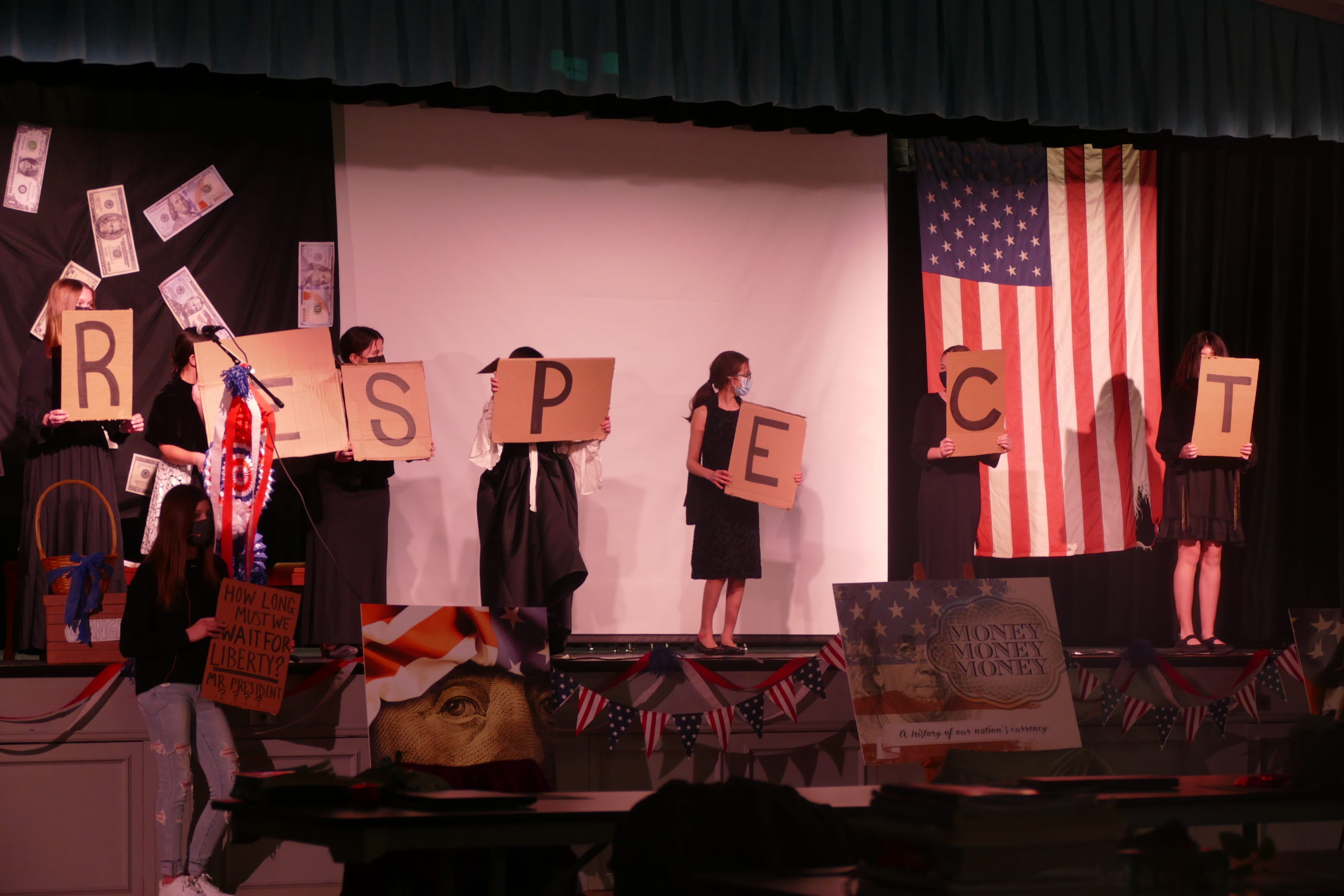 """Seventh grade girls closed the """"Money, Money, Money"""" assembly at Our Lady of the Hamptons with the suffragettes singing, """"R-E-S-P-E-C-T."""""""