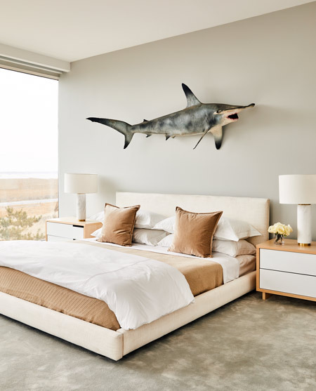 An unusual fiberglass shark adorns this bedroom on Dune Road in East Quogue; note the careful colorplay between the warm hued bedding and cool grey walls.