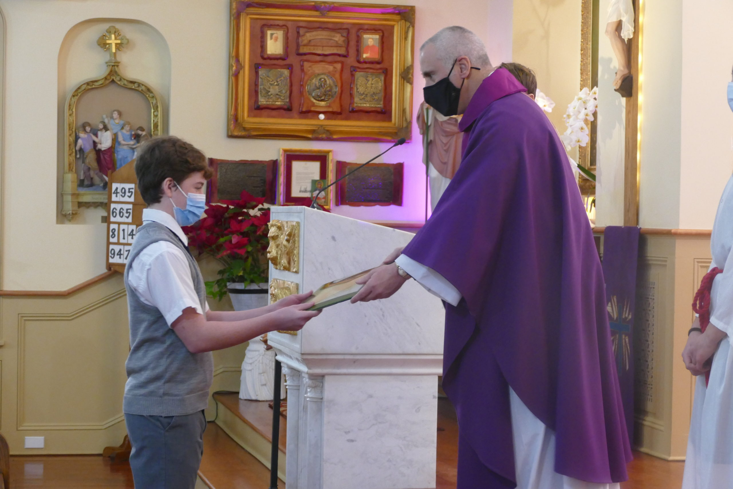 OLH Prep 8 student Jack Cantwell presents one of the offertory gifts to Father Maddaloni at the Lenten liturgy