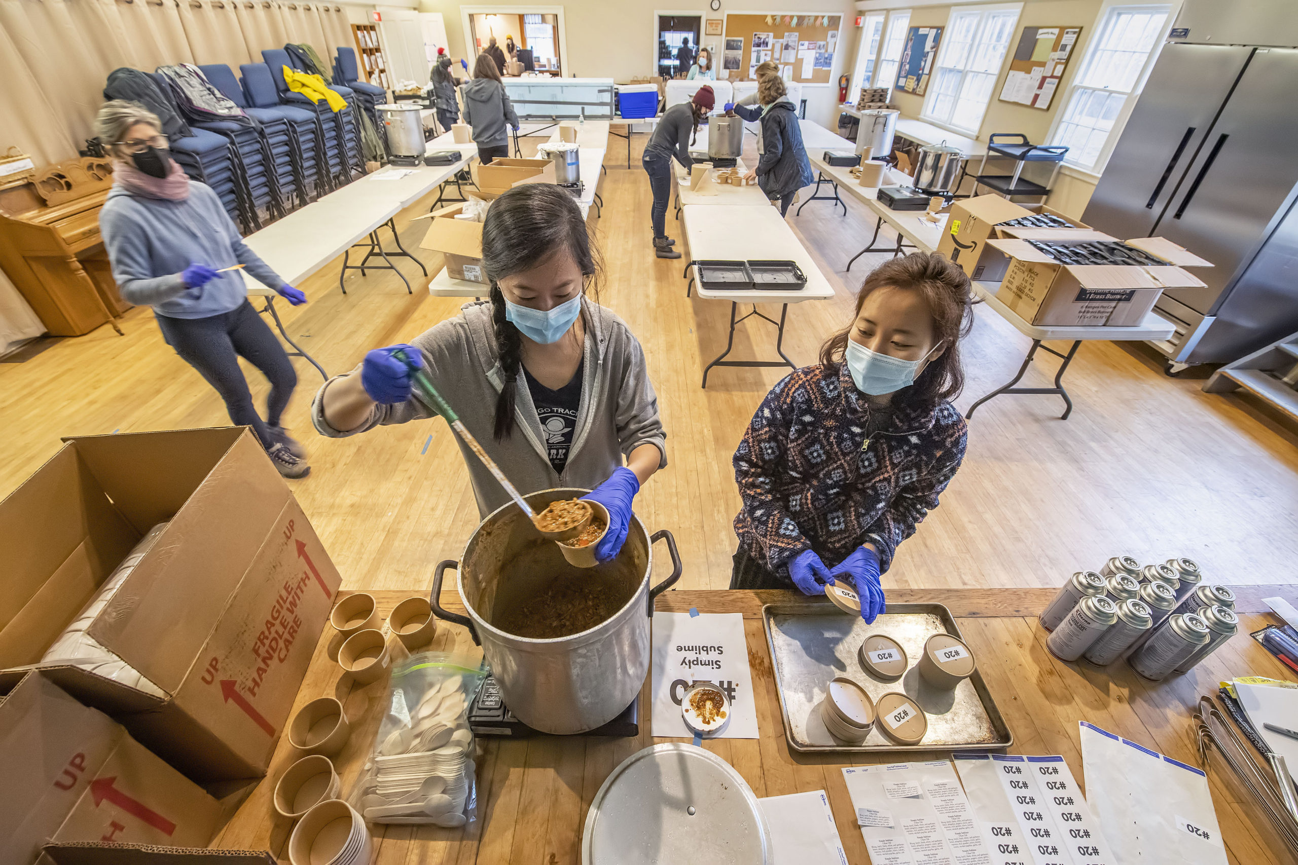 Elise Hsu and Jenny Park fill containers of chili made by Simply Sublime during the annual Chili Cook Off that was held at the Springs Presbyterian Church on Saturday.     MICHAEL HELLER