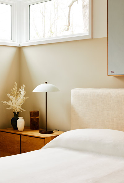 A two-tone beige wall adds warmth to a crisp guest bedroom.