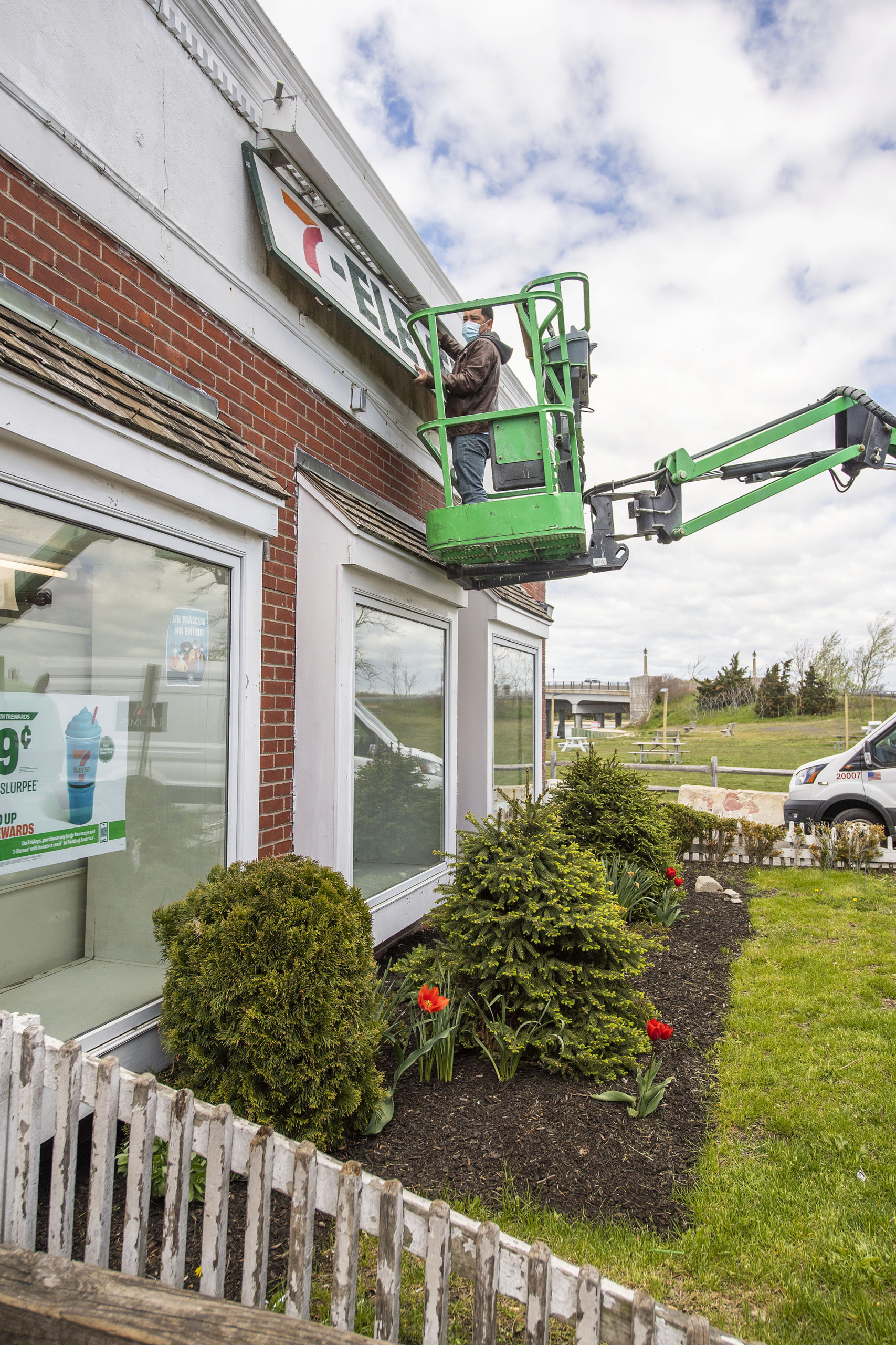 A worker removes the sign from the Sag Harbor 7-Eleven, which closed on Friday. MICHAEL HELLER