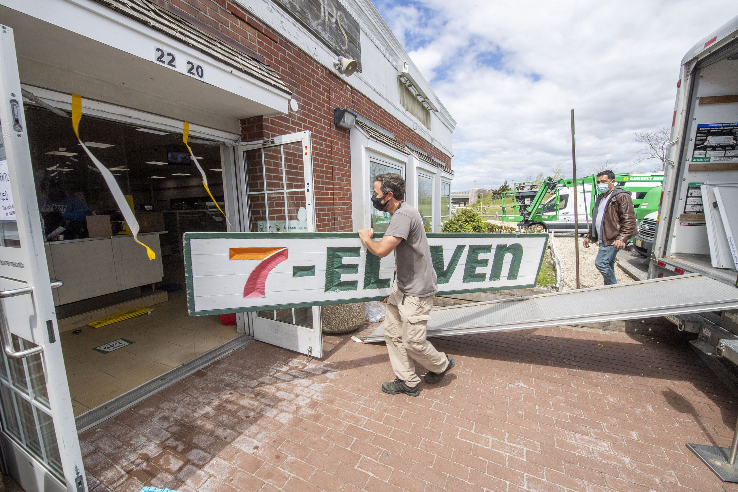 The sign above the 7-11 is taken down as the store was emptied and shut down on Friday. Michael Heller