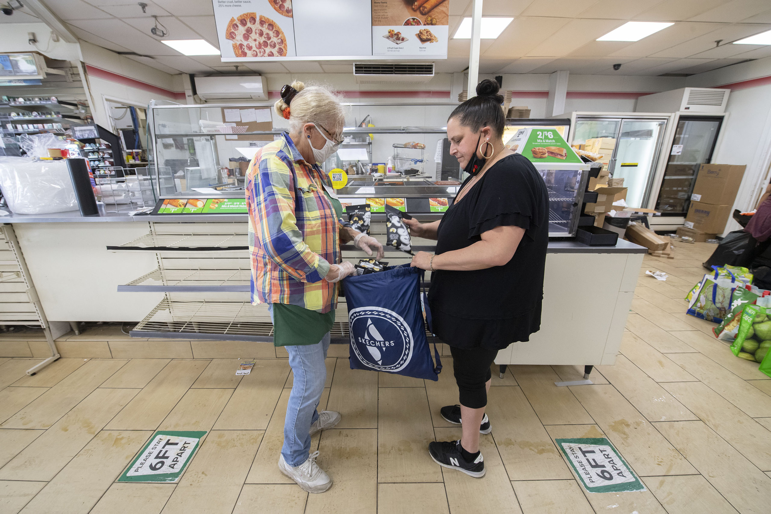 Cynthia Williams, one of 7-Eleven's managers, loads a bag of groceries donated to the Sag Harbor Food Pantry for volunteer Pam Kern. MICHAEL HELLER