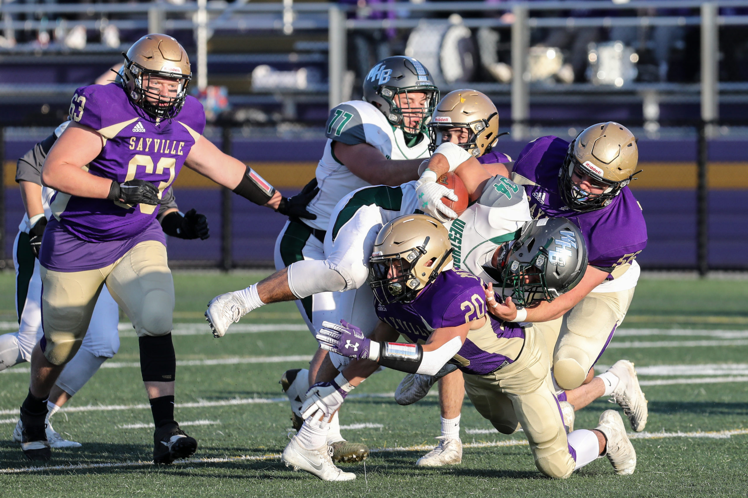 Dom Sarno of Westhampton Beach is tackled Sayville's C. J. Messina and another Golden Flash.