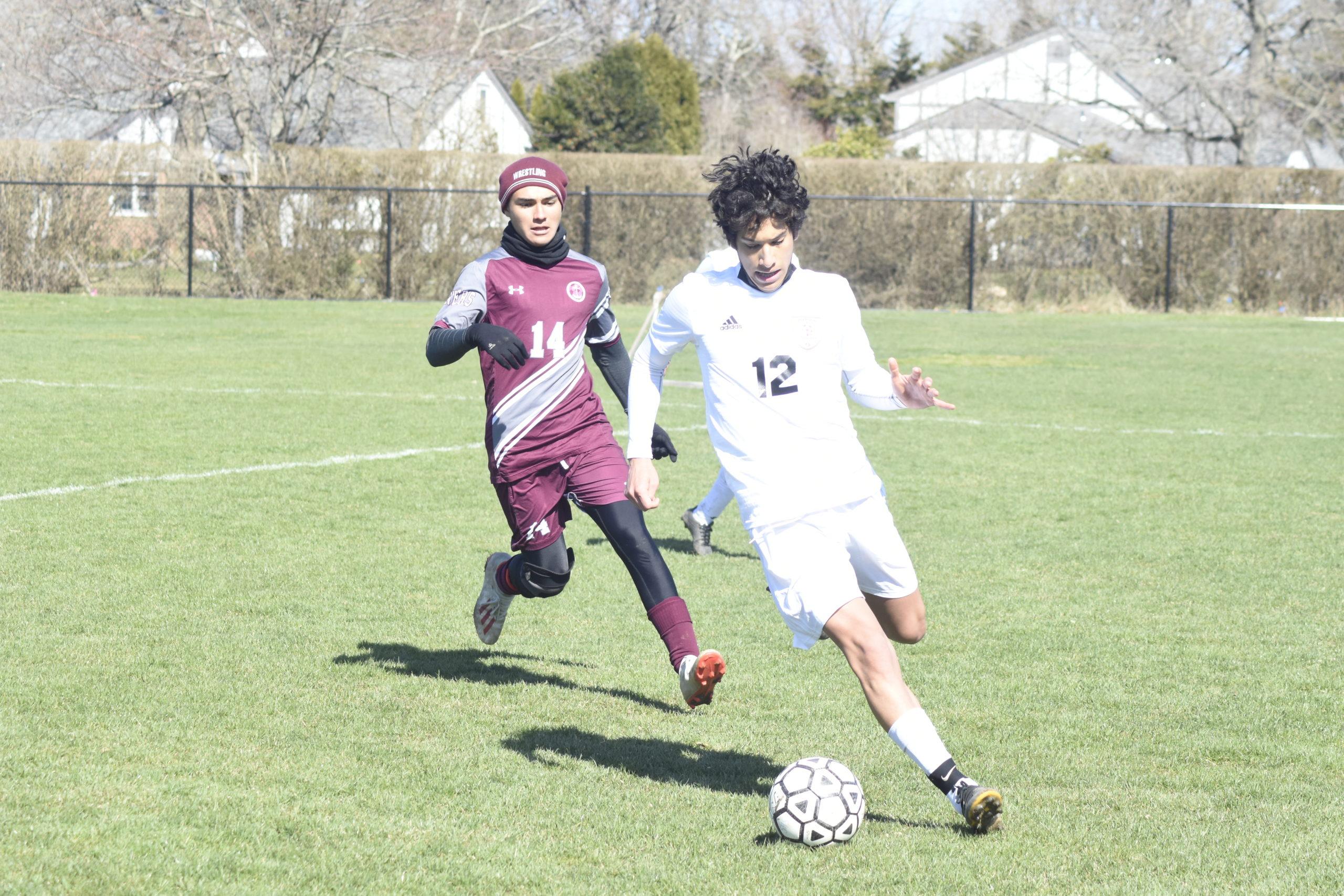 Pierson junior Daniel Martinez plays the ball near the sideline with Southampton junior Adrian Gonzalez trailing him.