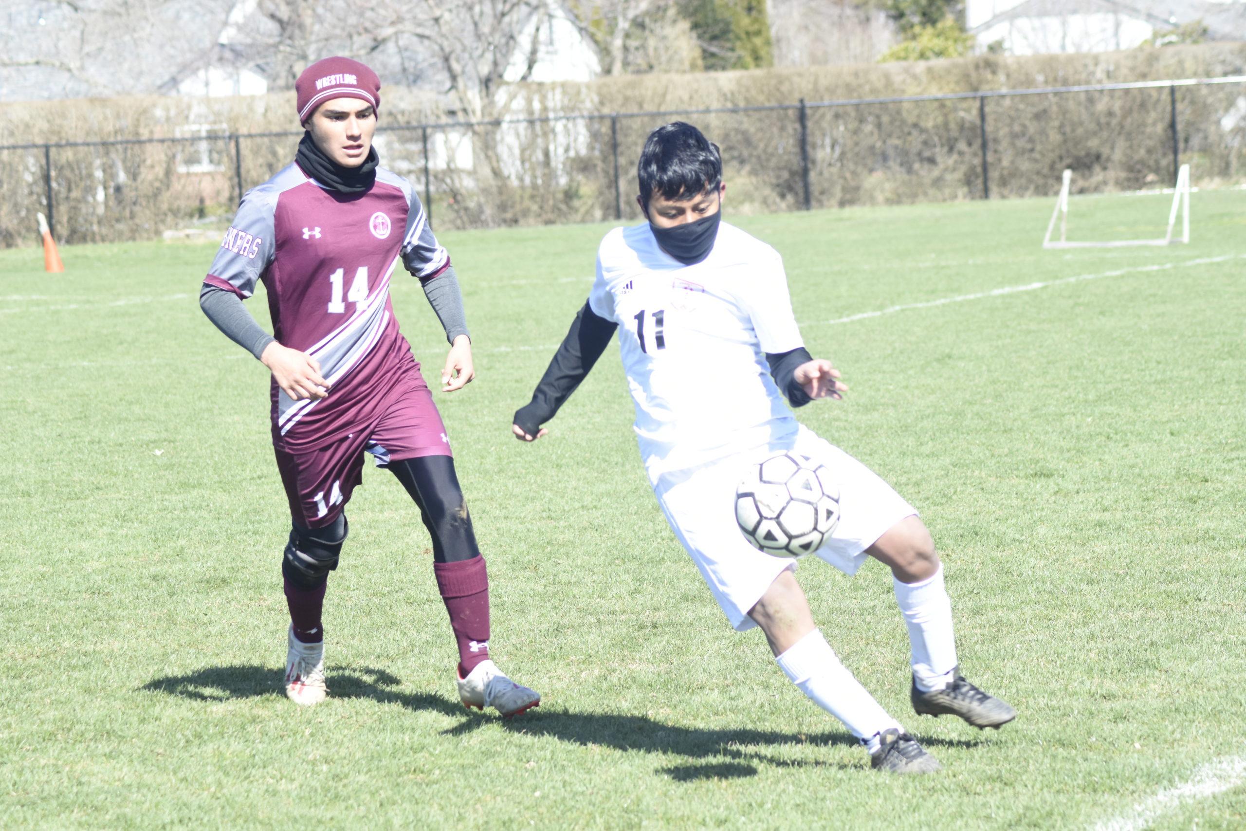 Bridgehampton junior Victor Paredes plays the ball near the sideline with Southampton junior Adrian Gonzalez trailing him.