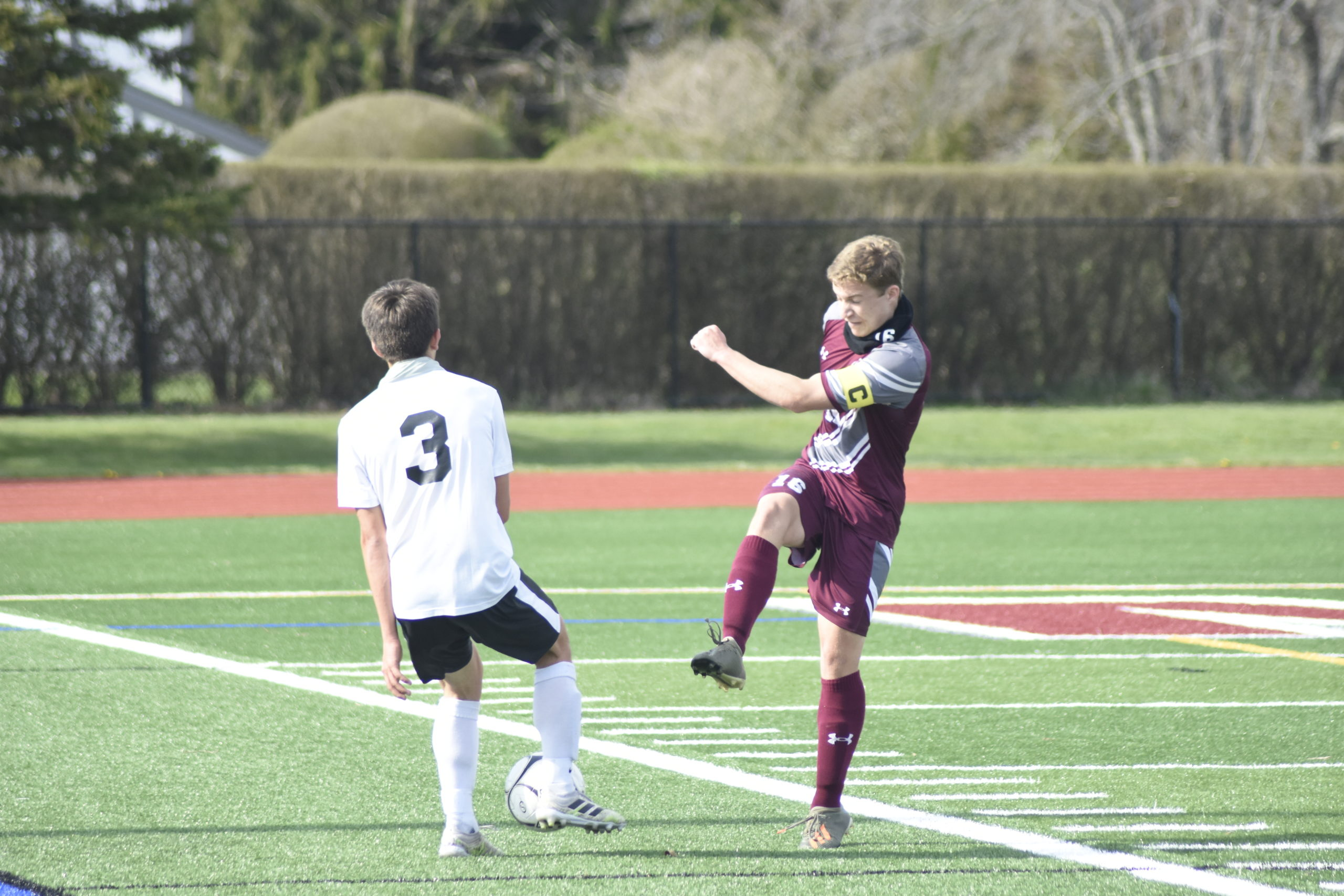 Southampton junior captain Turner West tries to clear the ball out of his defensive end but Babylon sophomore Nick Giammarino is there to block it.