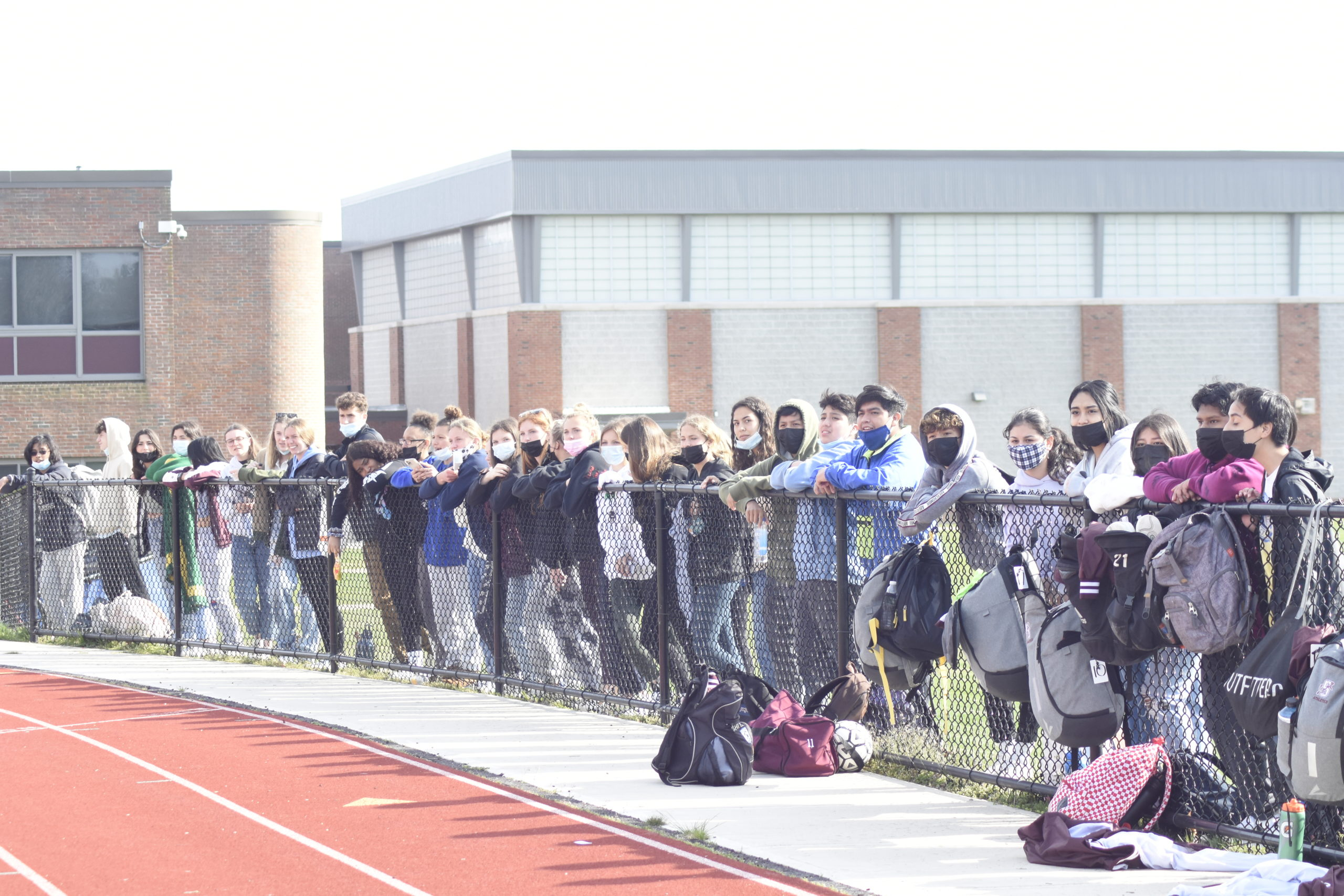 Southampton students line the outside of the track, cheering on their classmates in Wednesday's boys soccer playoff game.