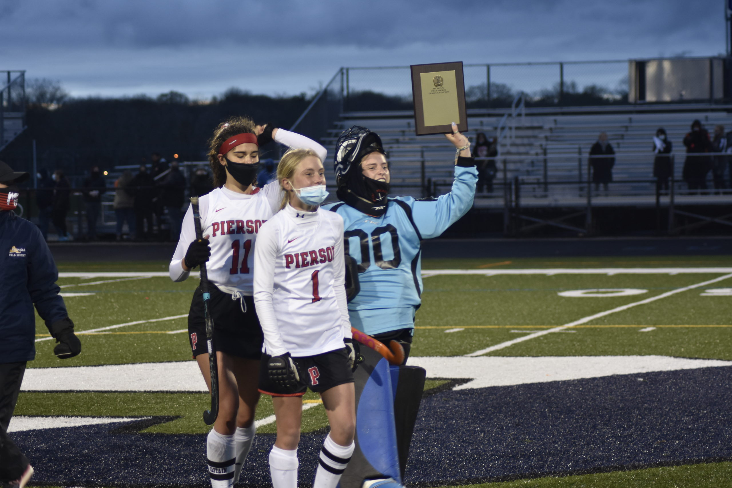 Pierson tri-captains, from left, Meredith Spolarich, Brooke Esposito and Grace Perello hoist the county championship plaque.