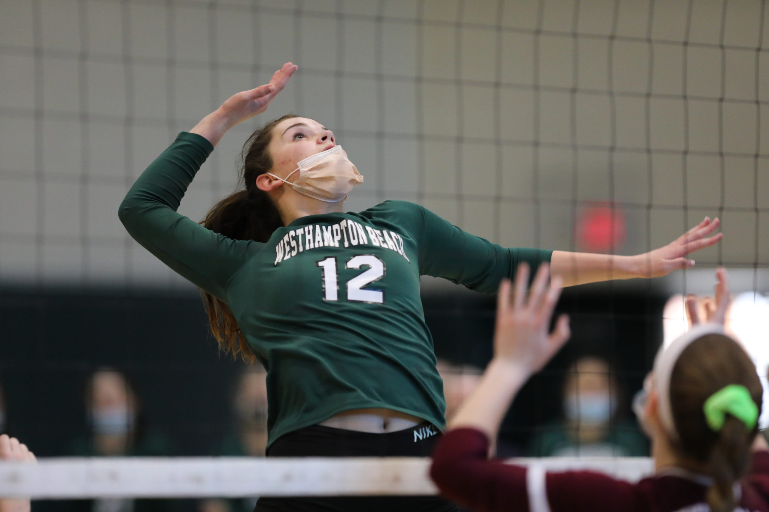 Westhampton Beach senior Ella Donneson leaps to the top of the net to spike the ball.