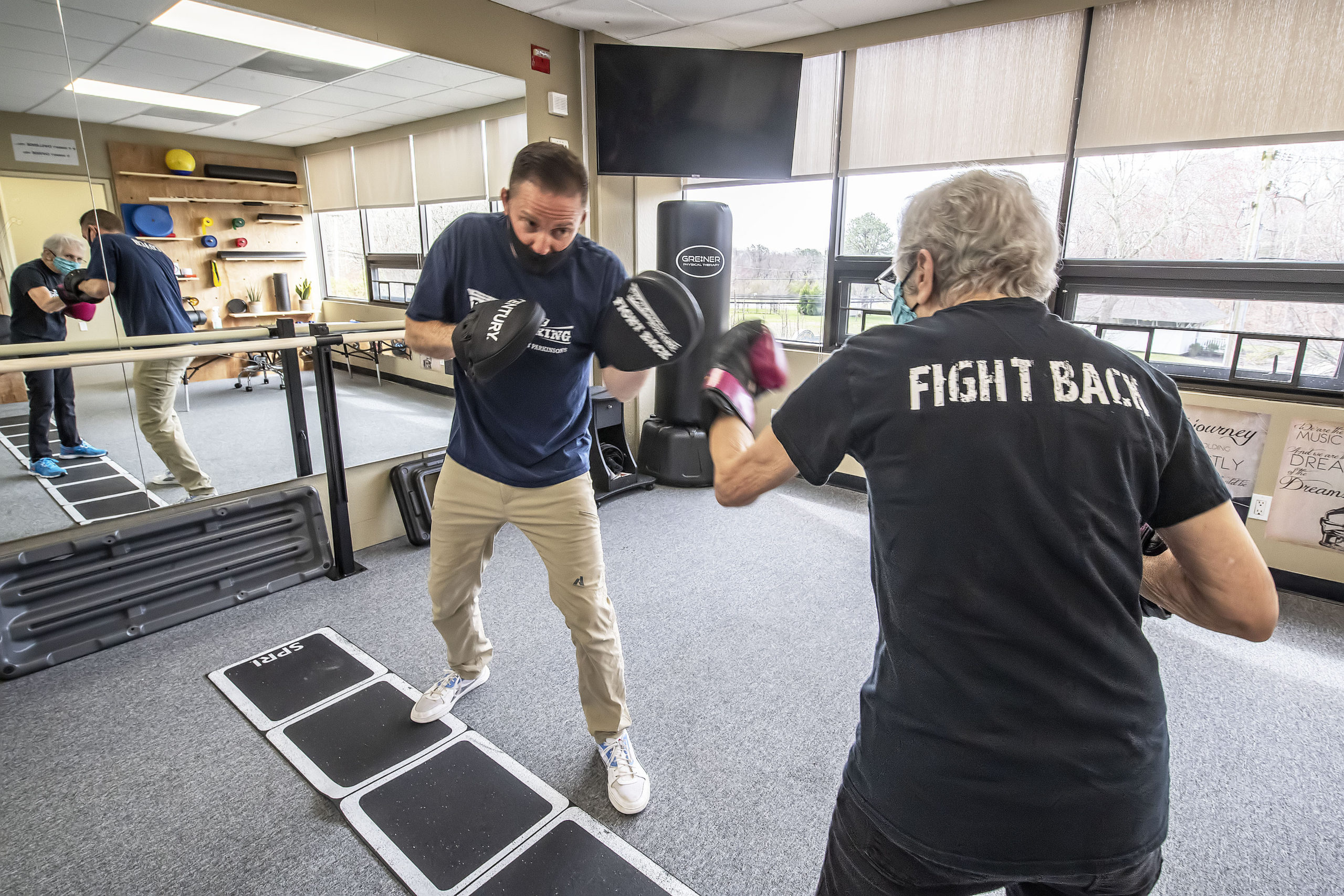 Seth Greiner of Greiner Physical Therapy does a Rock Steady Boxing workout with Parkinson's patient Janet Barr at the Greiner Physical Therapy studio in Speonk.