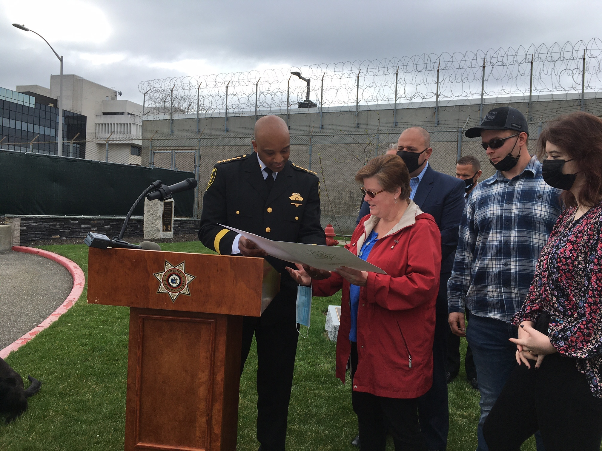 Sheriff Errol D. Toulon Jr. presents Stacey Reister and family with a proclamation .