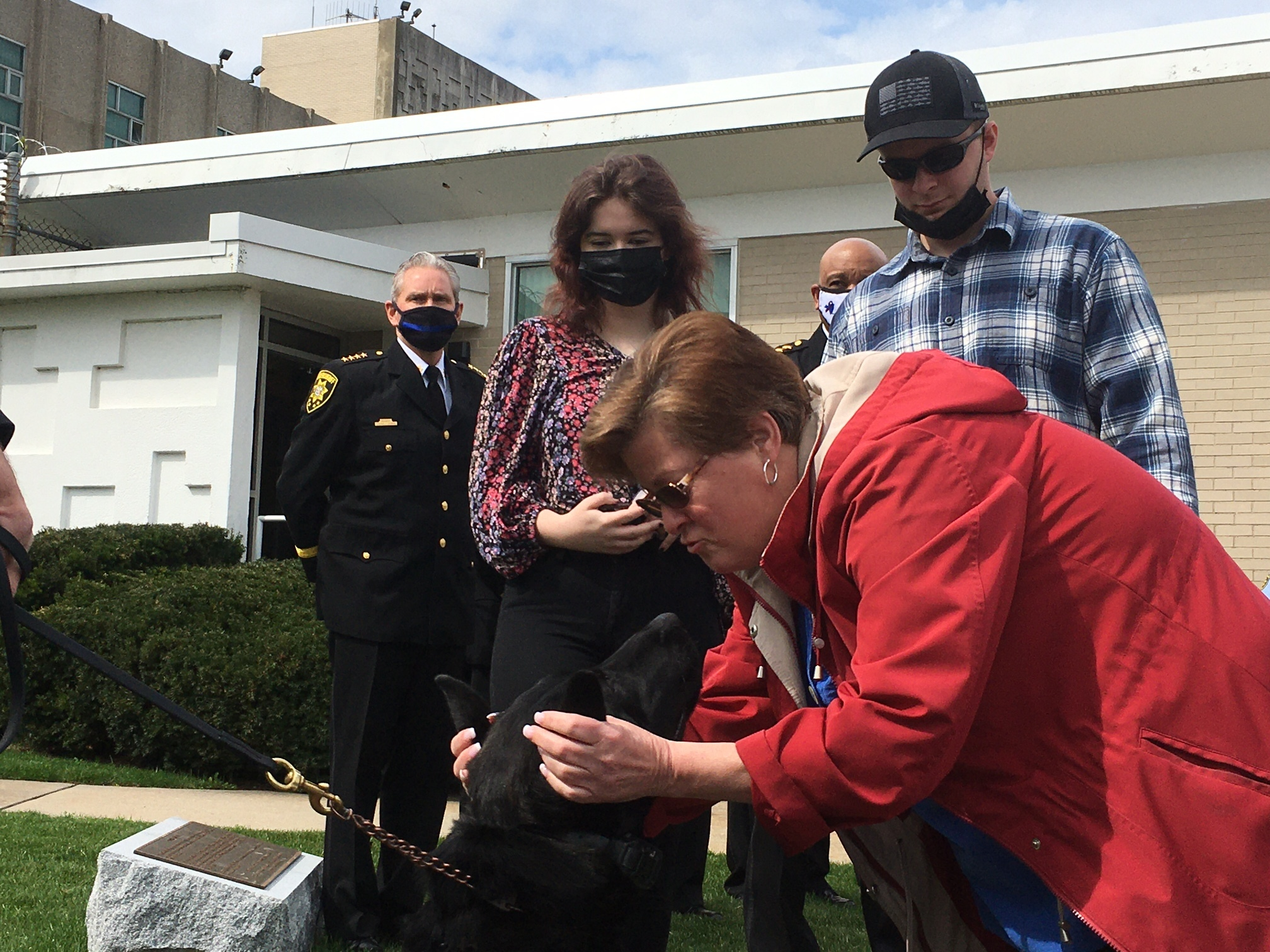Stacey Reister gives K-9 Reis some love as her children Mary and Davd look on.