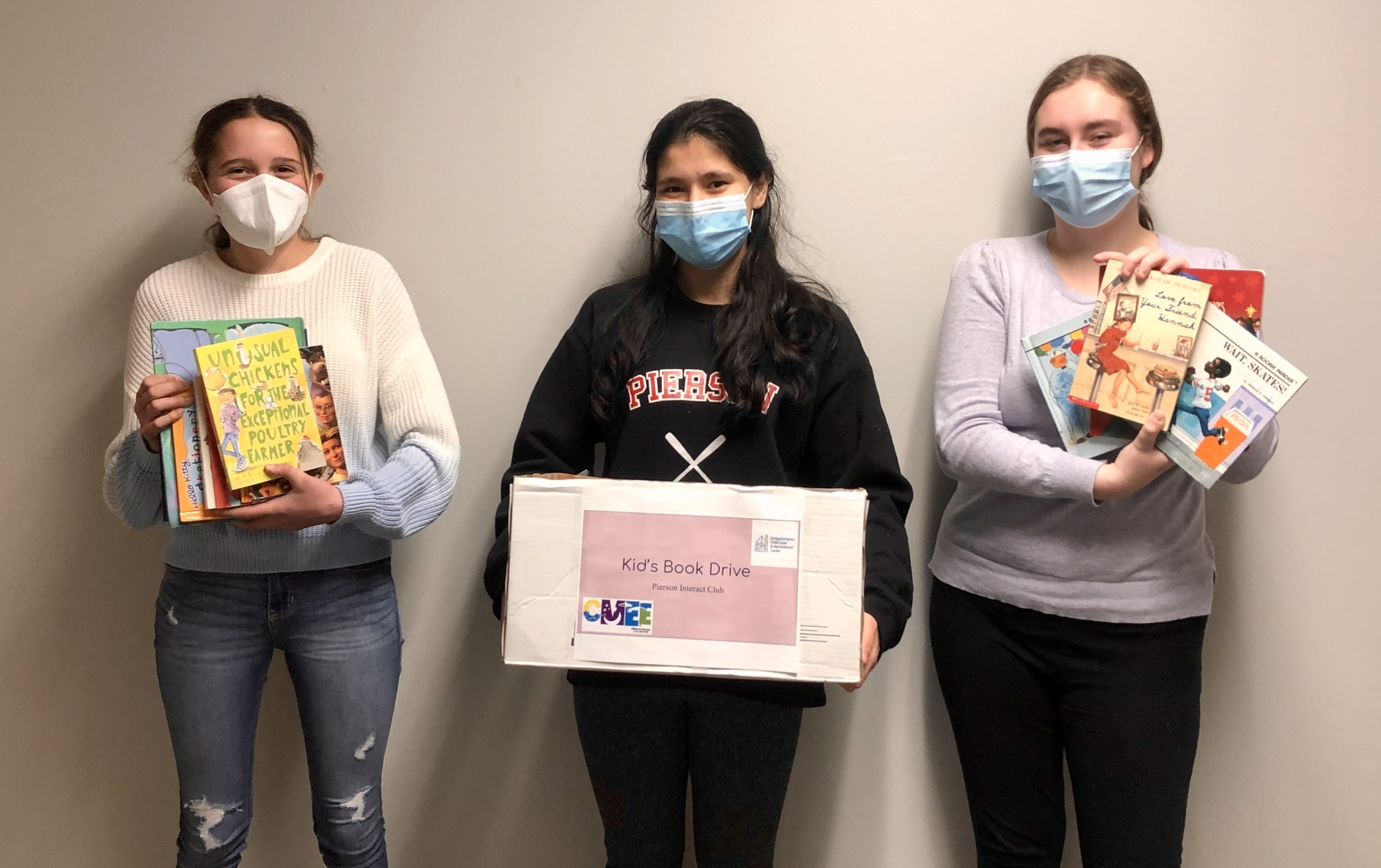 From left, Interact Club members Izzy Caplin, Ava Garabedian and Olivia Martin, collected book donations at Pierson High School to support the Bridgehampton Childcare Center.