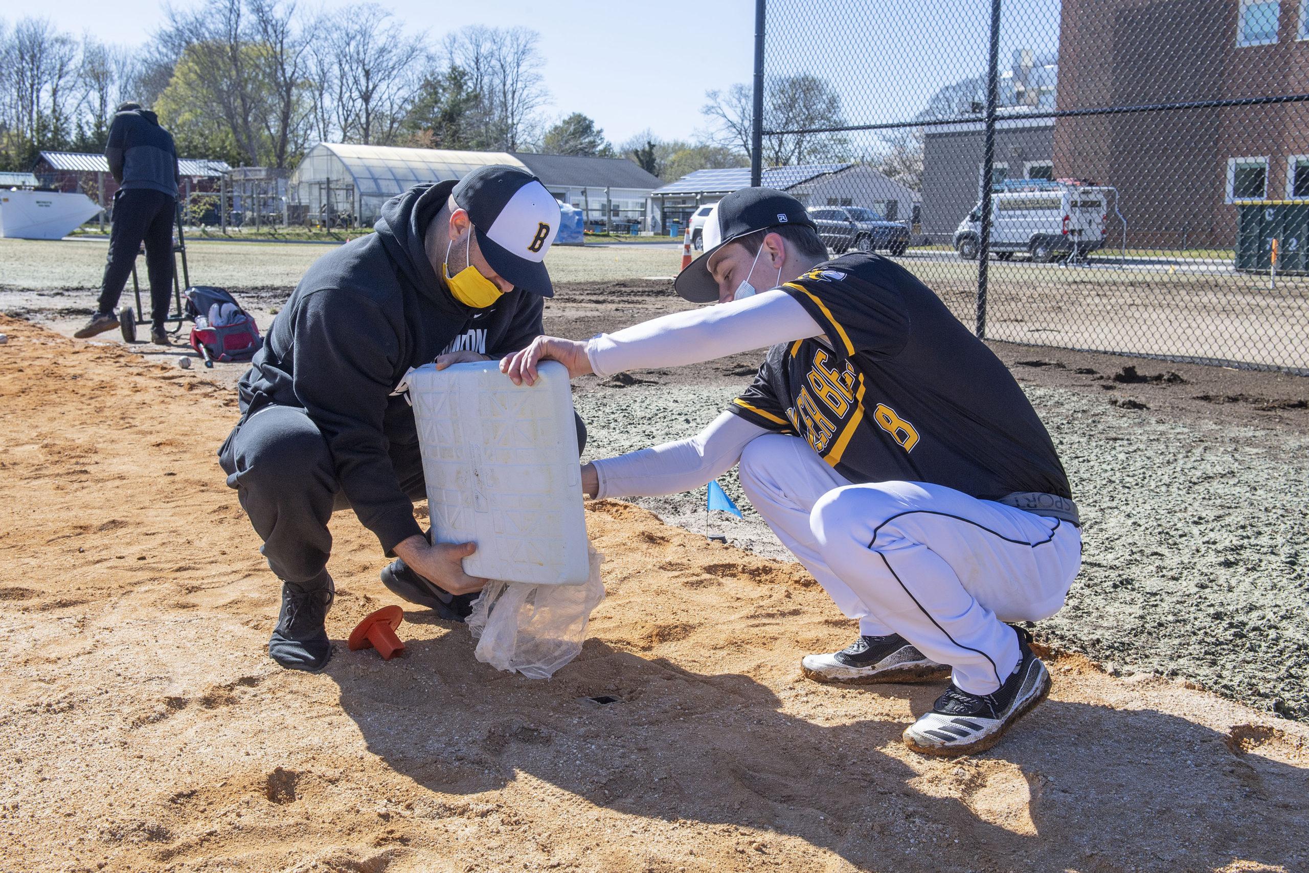 Assistant coach Michael DeRosa, left, and co-captain Scott Vinski set the bases as the Bridgehampton baseball team prepares for its first practice of the season. MICHAEL HELLER