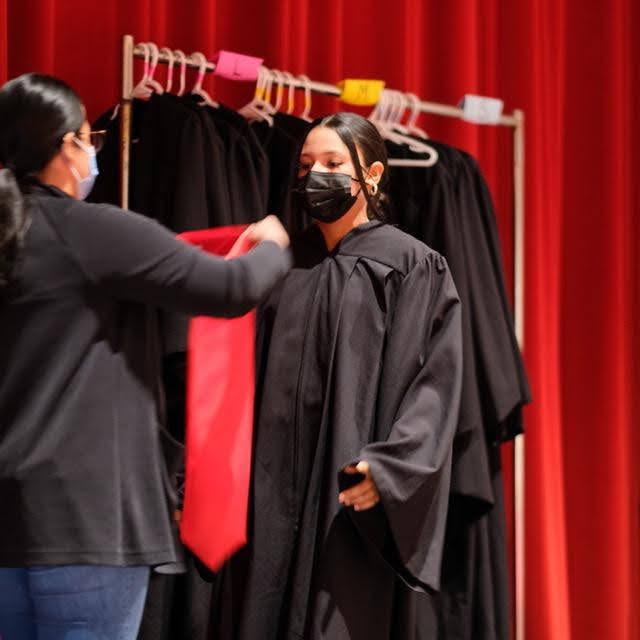Pierson teacher Veronica Rodriguez helped Juliana Barahona De La Cruz prepare for her portrait.