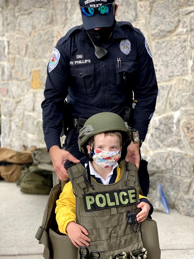Pre-K student, Adler Kanas, tries on the protective gear used by Southampton Town Police Officers during Raynor Country Day School's Police Expo.