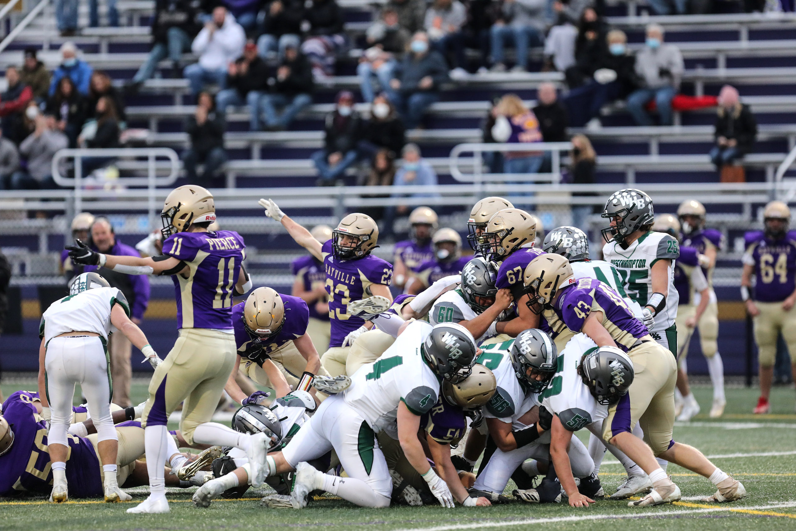 Westhampton Beach and Sayville football players pile up on a loose ball.