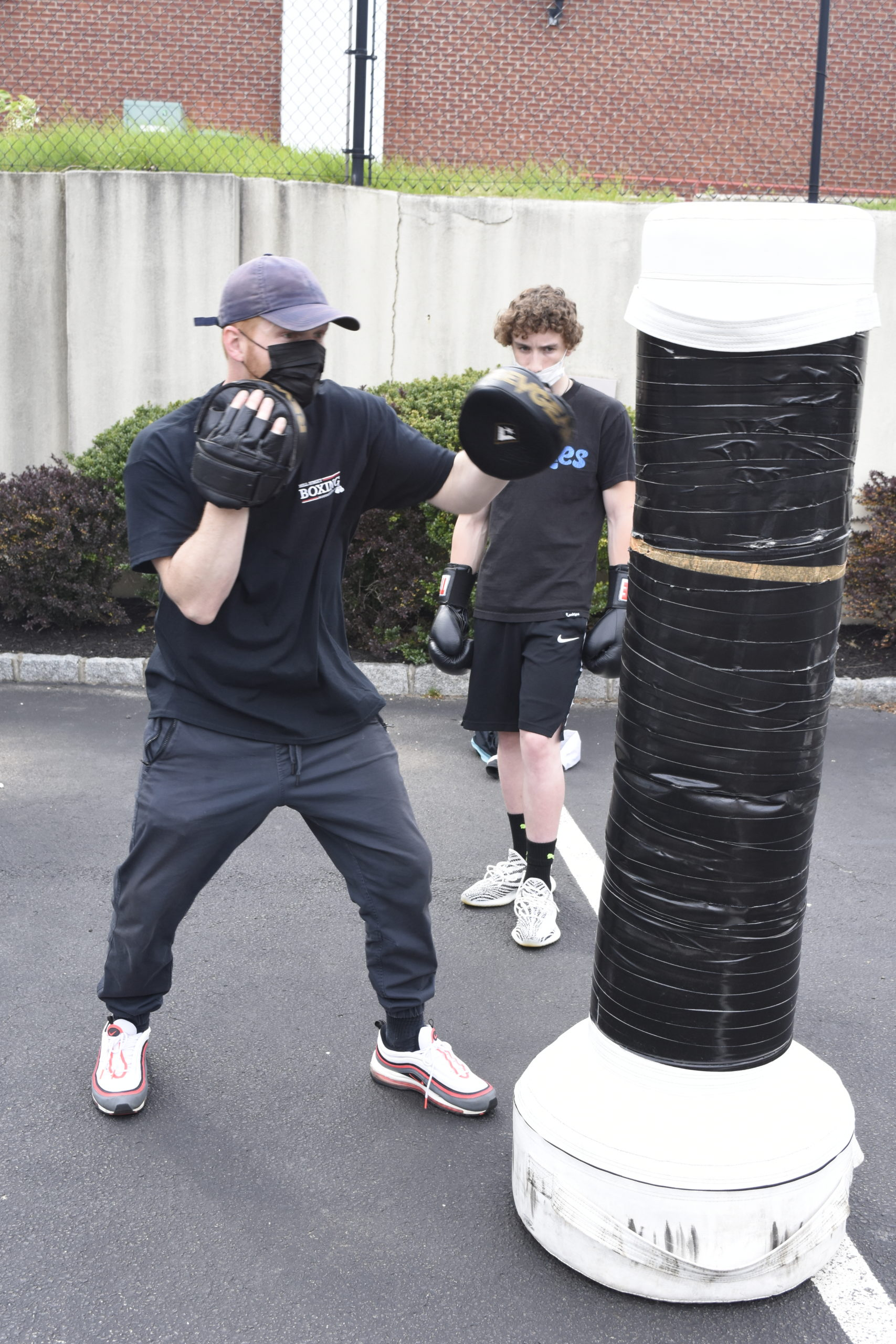 Avery Crocker shows Hampton Bays student Chandler Tuttle some boxing techniques.