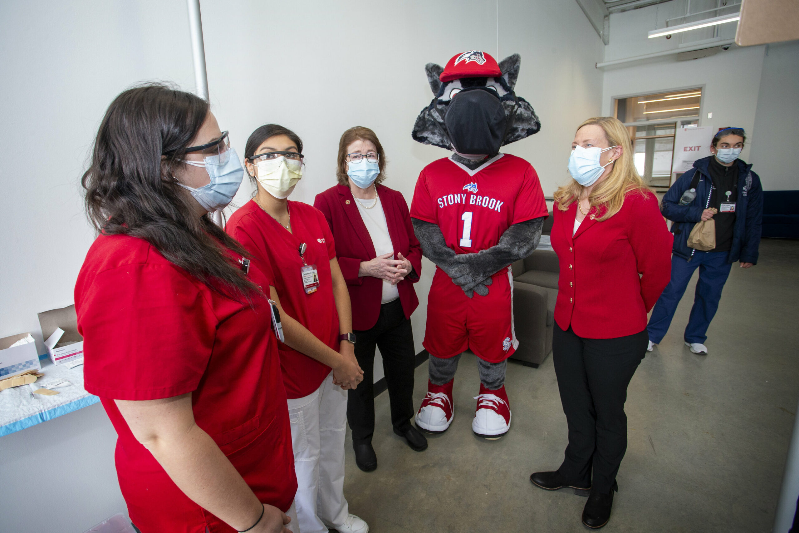 Dr. Maurie McInnis, President Of Stony Brook University, Wolfie and Dr. Margaret McGovern, Stony Brook Medicine Vice President for Health System Clinical Programs and Strategy, thank healthcare workers giving their time to help vaccinate Long Island.