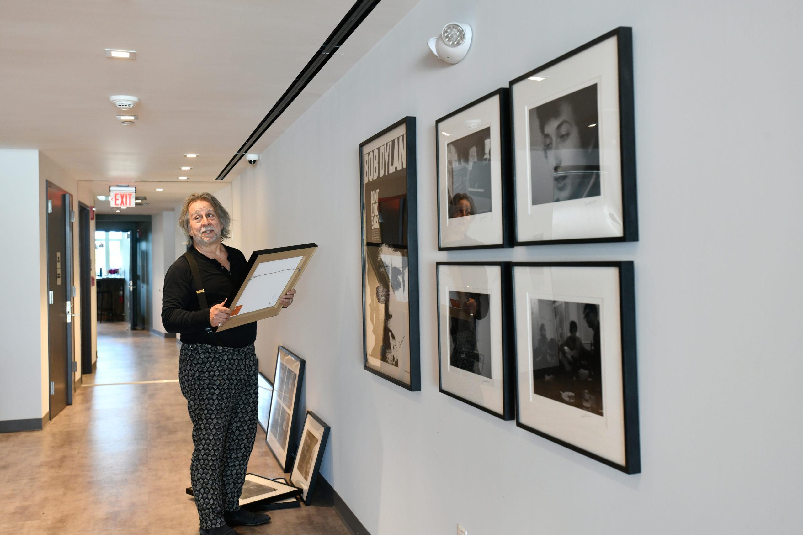 Joseph Baldassare, proprietor of Arthouse 18, hangs stills from the film