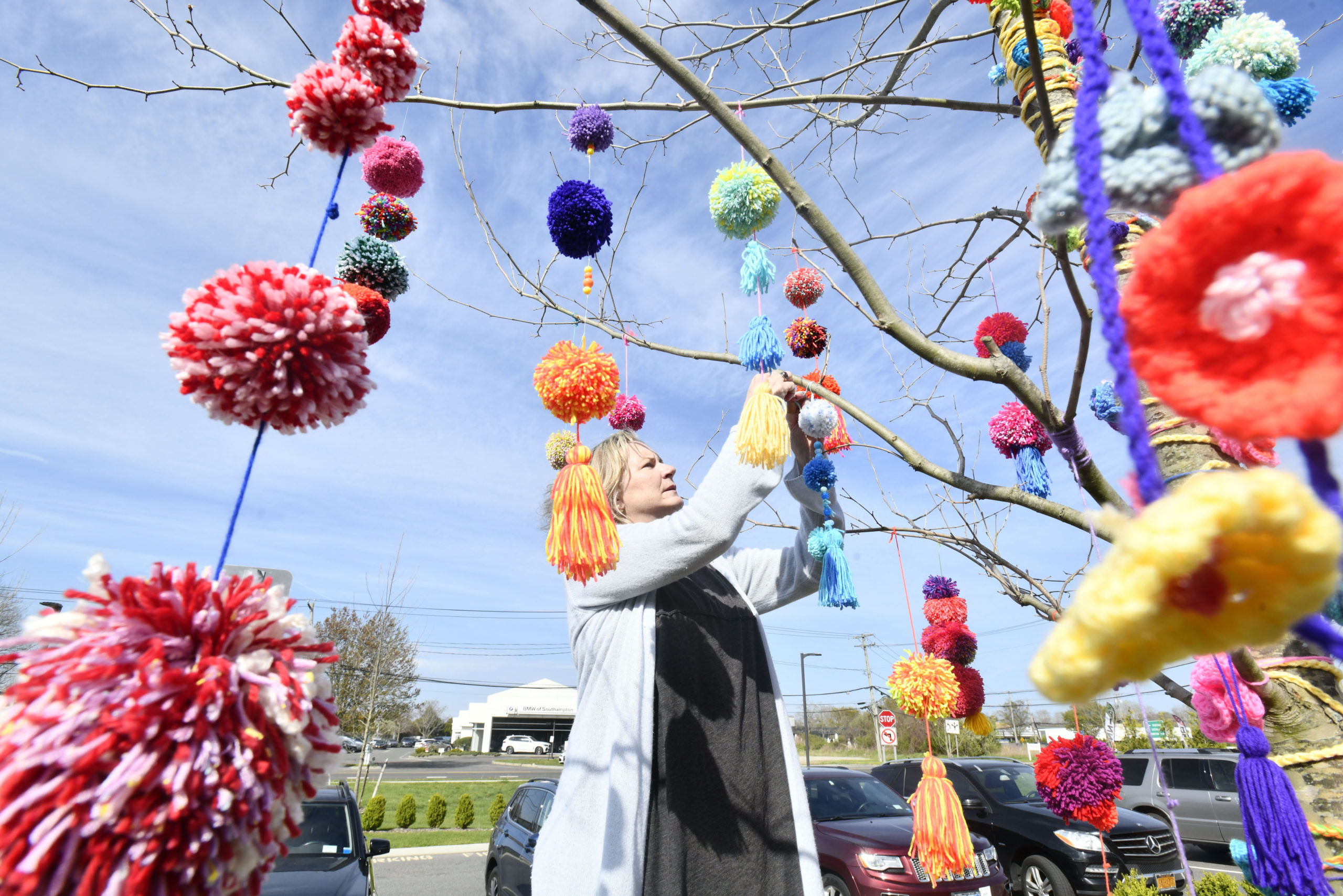 Mary Alyce Rogers hangs yarn tassels from a tree at the Phillips Family Cancer Center on Sunday afternoon. Members of the Coalition for Women's Cancers at Stony Brook Southampton Hospital put up the temporary