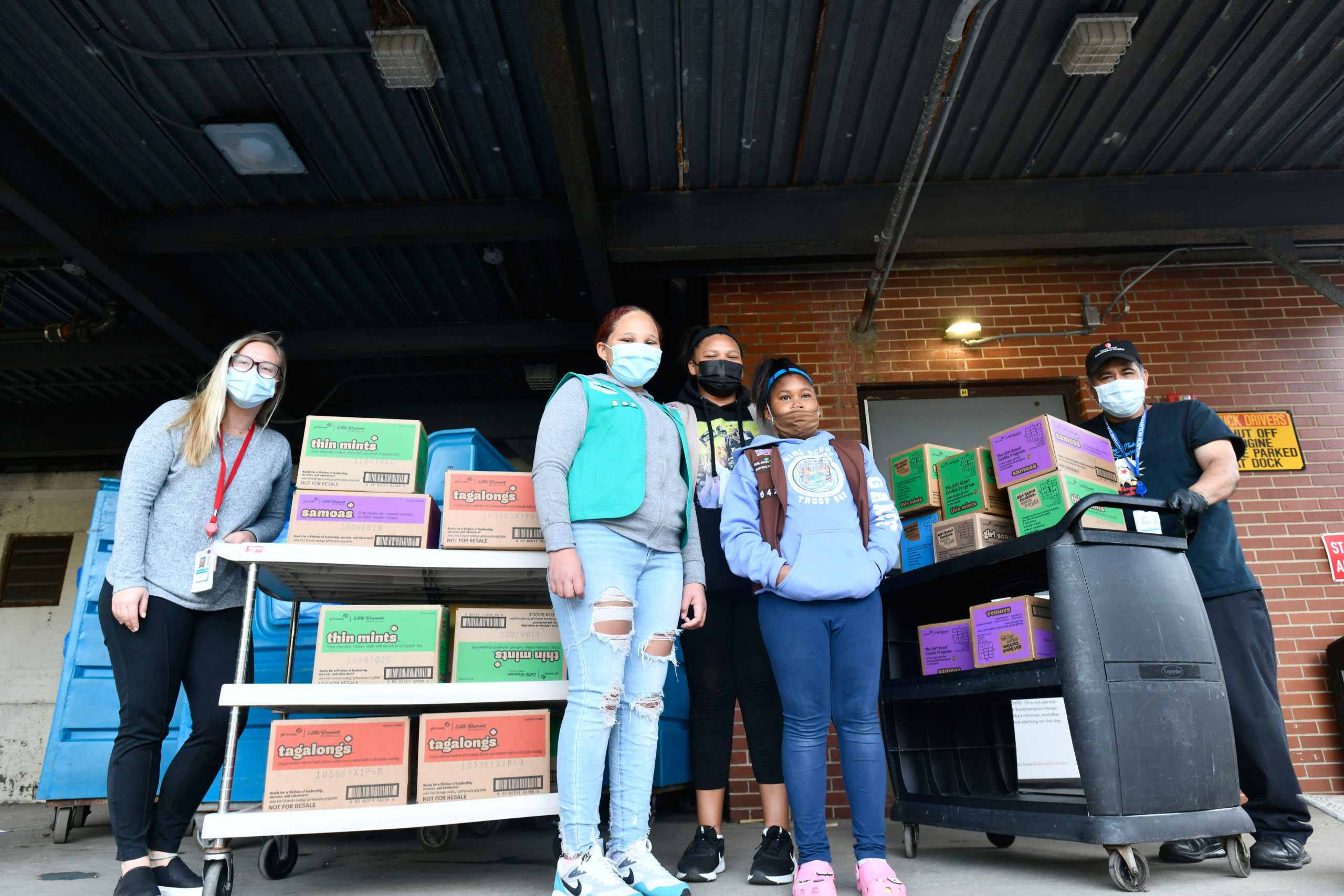 Members of Girl Scout Troop 642, Gabriella Gaines, Syvana Smith and Jordyn Smith, from the Shinnecock Nation dropped off 300 boxes (25 cases) of Girls Scout Cookies for the employees at Stony Brook Southampton Hospital on Sunday. May 2. Helping the girls unload are hospital employees Victoria Stanek and Cesar Flores.  DANA SHAW