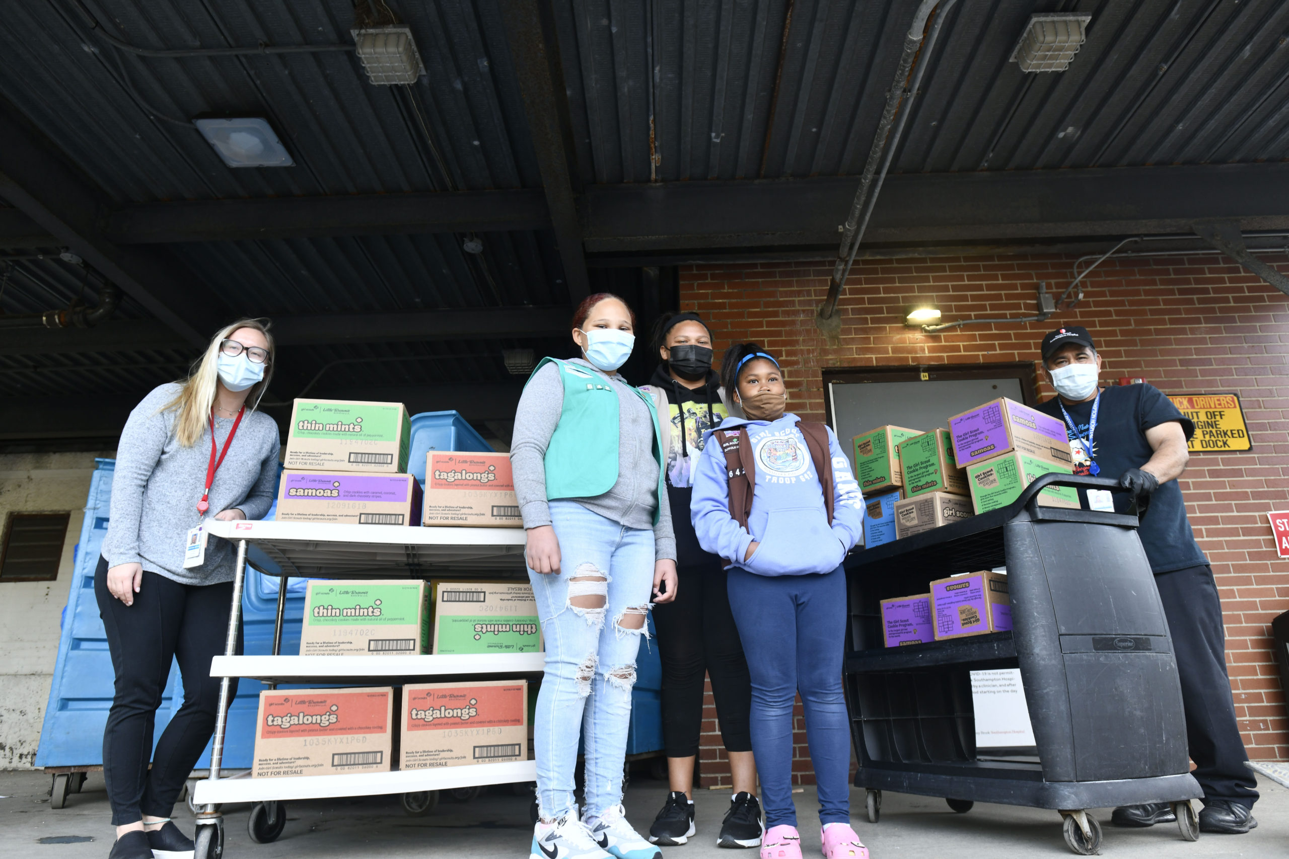 Members of Girl Scout Troop 642, Gabriella Gaines, Syvana Smith and Jordyn Smith, from the Shinnecock Nation dropped off 300 boxes (25 cases) of Girls Scout Cookies for the employees at Stony Brook Southampton Hospital on Sunday afternoon. Helping the girls unload are hospital employees Victoria Stanek and Cesar Flores.  DANA SHAW