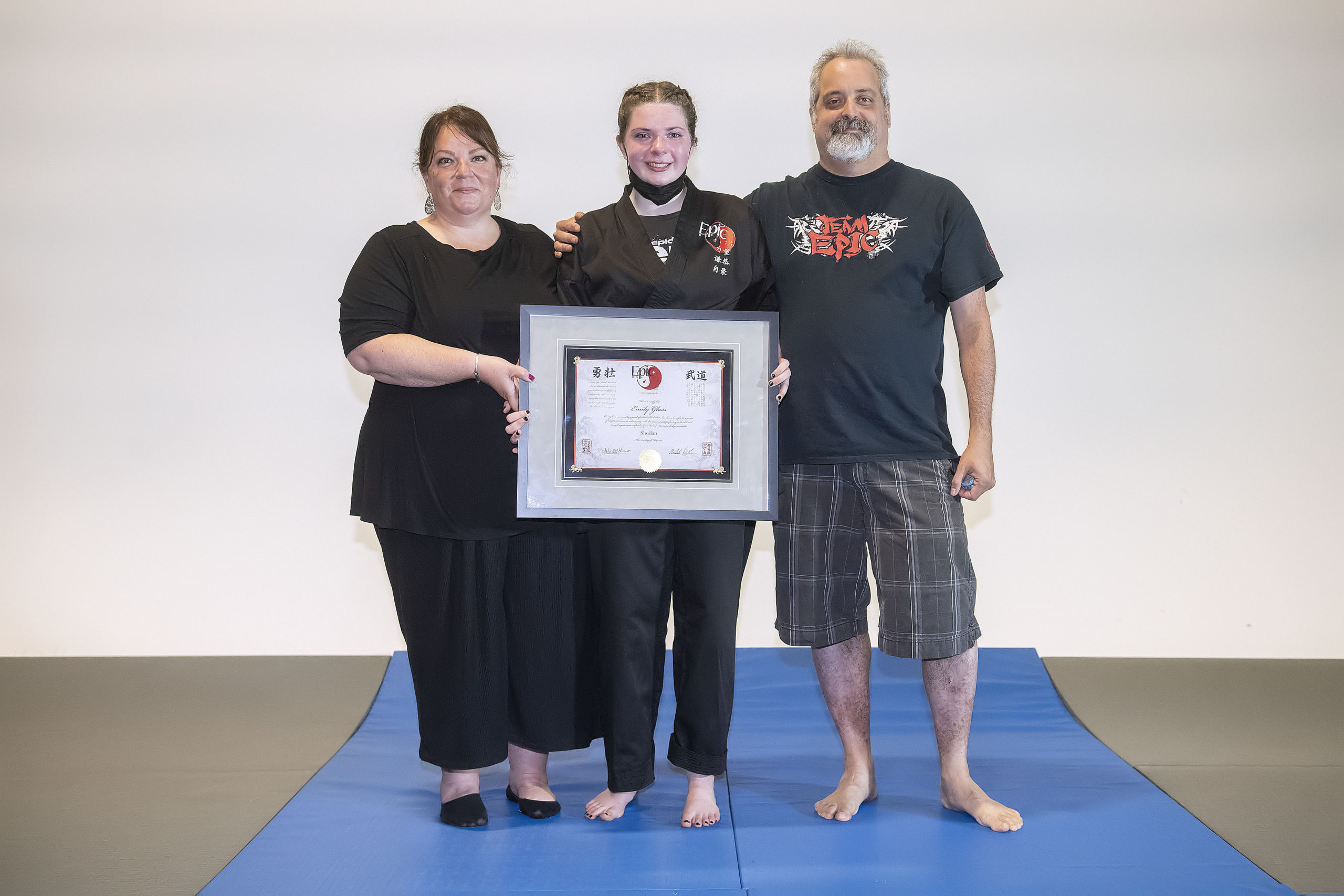 Emily Glass with her parents Jennifer and Dan after receiving her black belt on Sunday.