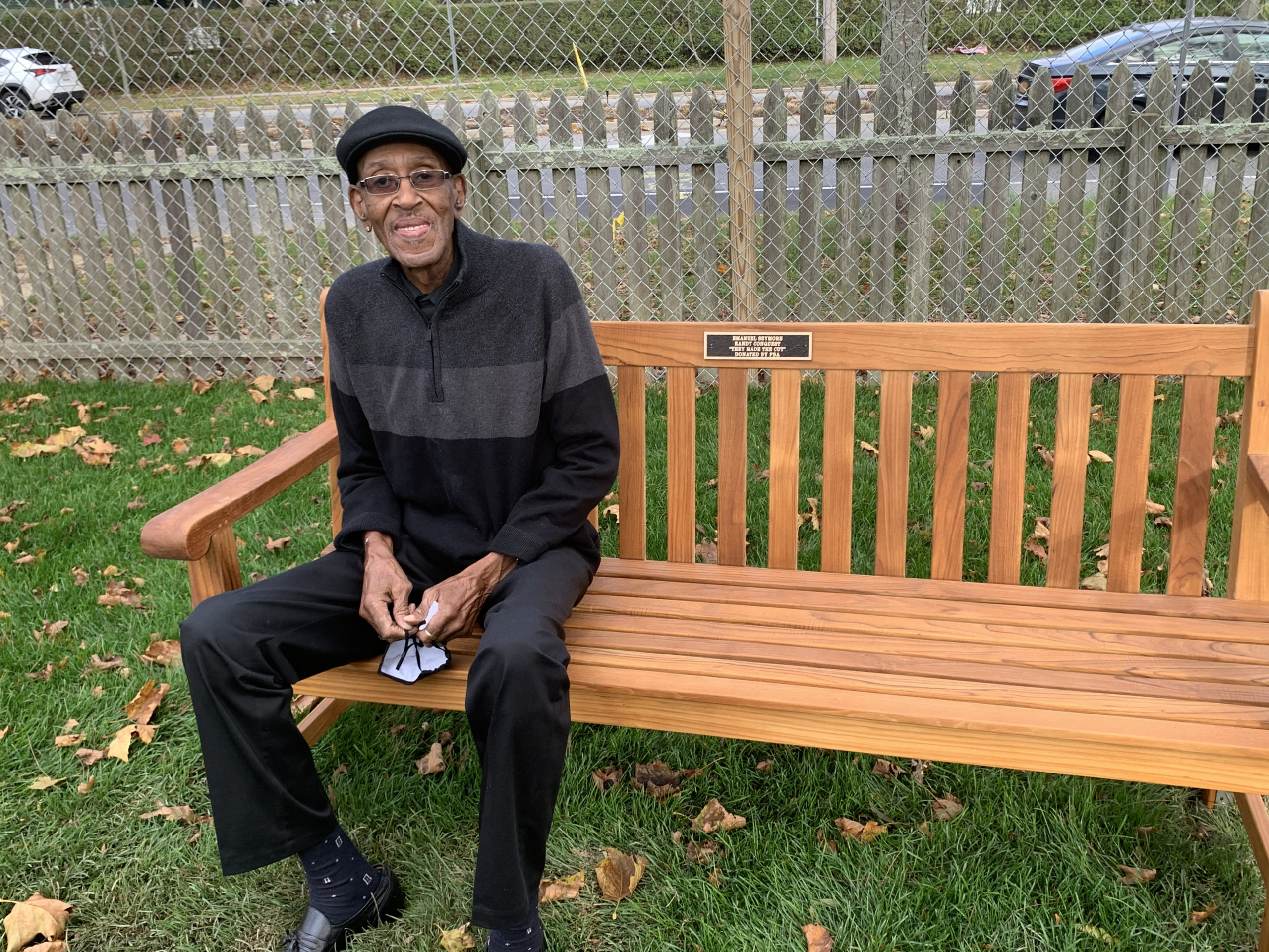 Randy Conquest on a bench dedicated to him and Emanuel Seymore, on the grounds of the Southampton African American Museum.  COURTESY BRENDA SIMMONS