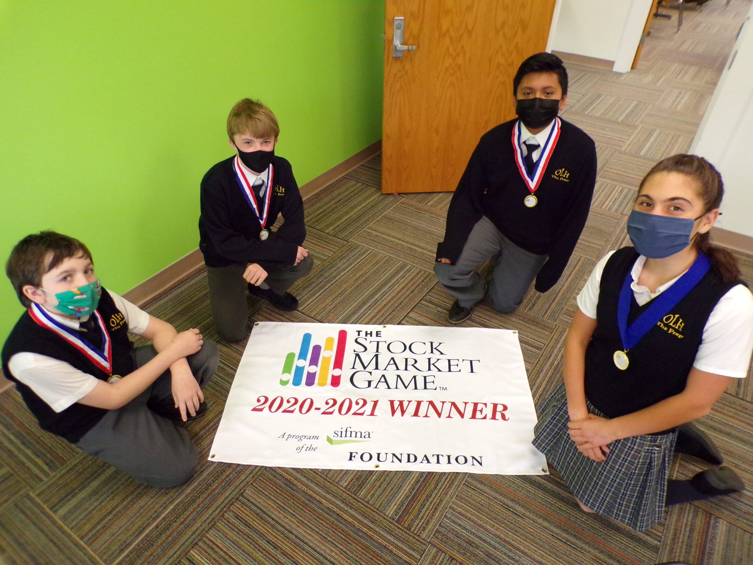 (From left to right) Luke David, George McDonald, Jake Morales and Maxine Boeding. Maxine placed first place in the SIFMA Foundation's Stock Market Game, with the rest of the students taking a second place award.