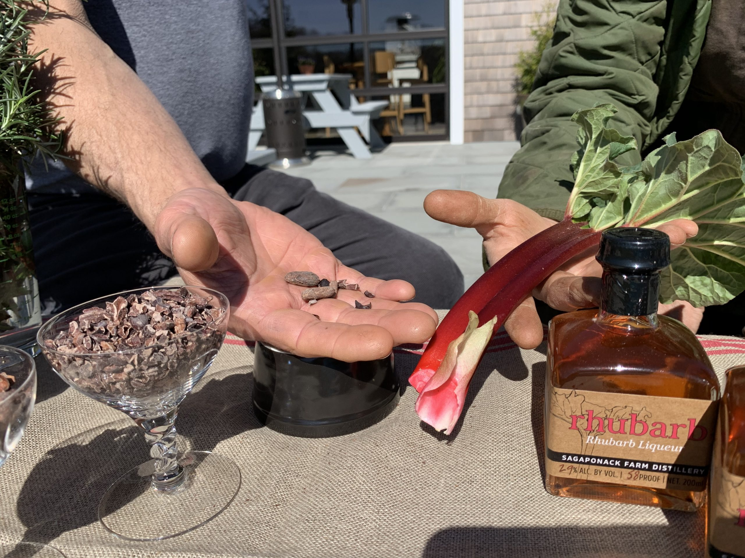 """Chef Steven Amaral and Marilee Foster hold ingredients at  Sagaponack Farm Distillery for their new chocolate bars — the """"Whiskey Bar"""