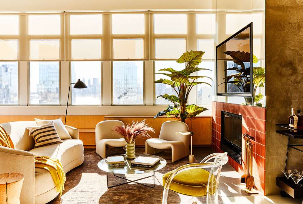 A floating contemporary curved sofa is bathing in golden hour sunlight in this recently renovated historic home. CHRISTIAN HARDER