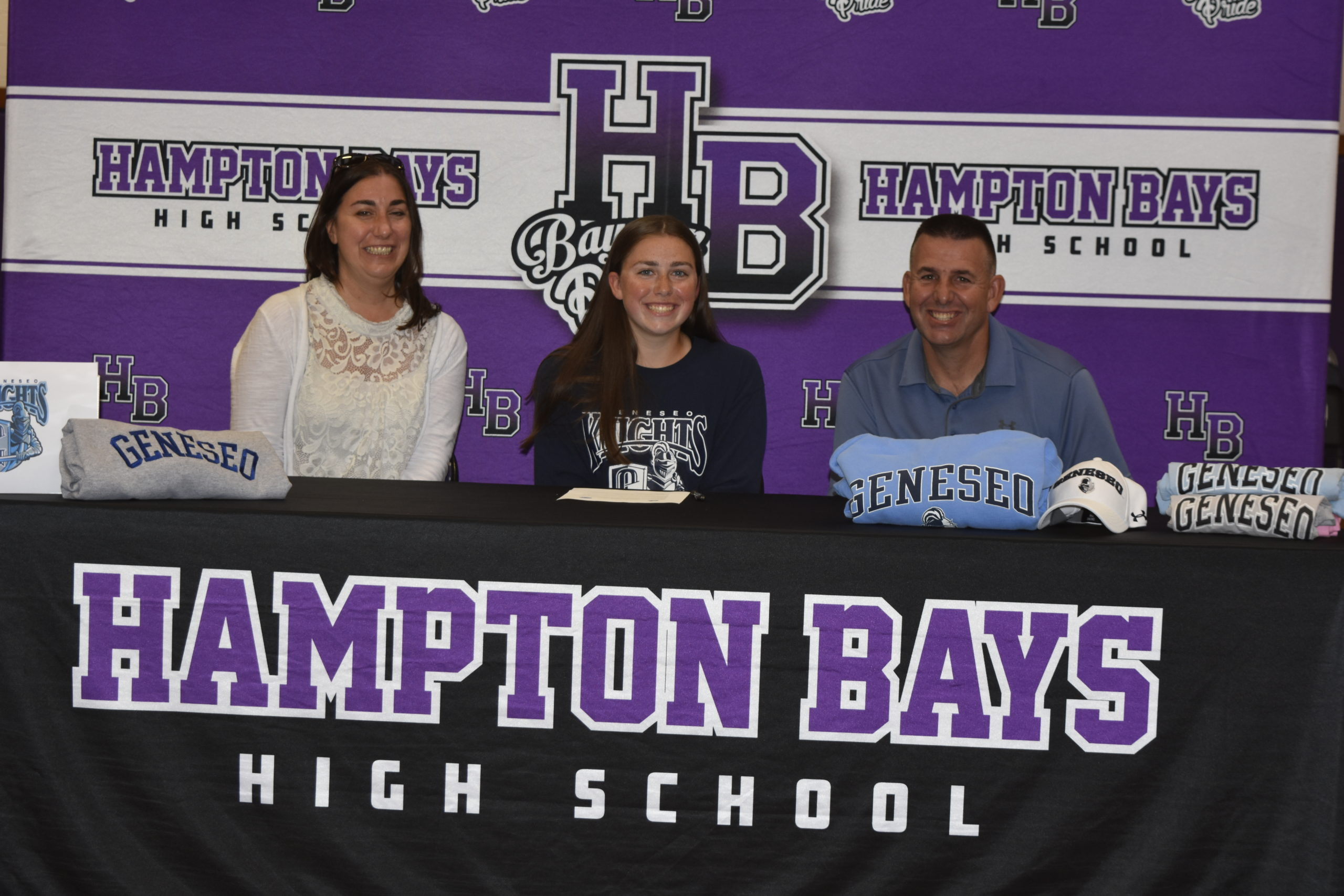 Tara Brochu with her parents, Paul and Tara, signing her letter of intent to play softball at SUNY Geneseo on June 1.