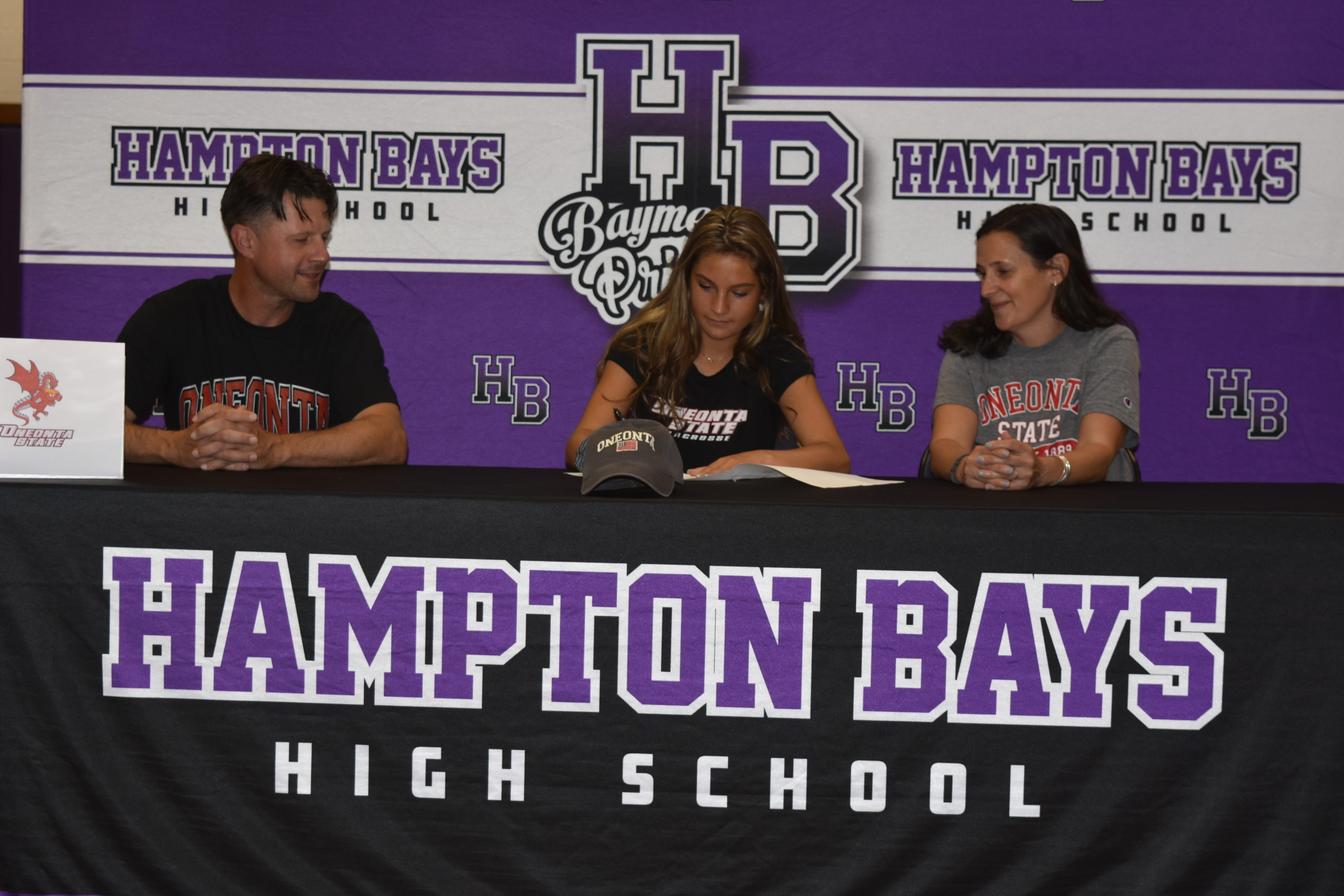Cassidy Moore, with her parents,  Vinny and Dawn, signing her letter of intent to play lacrosse at SUNY Oneonta.
