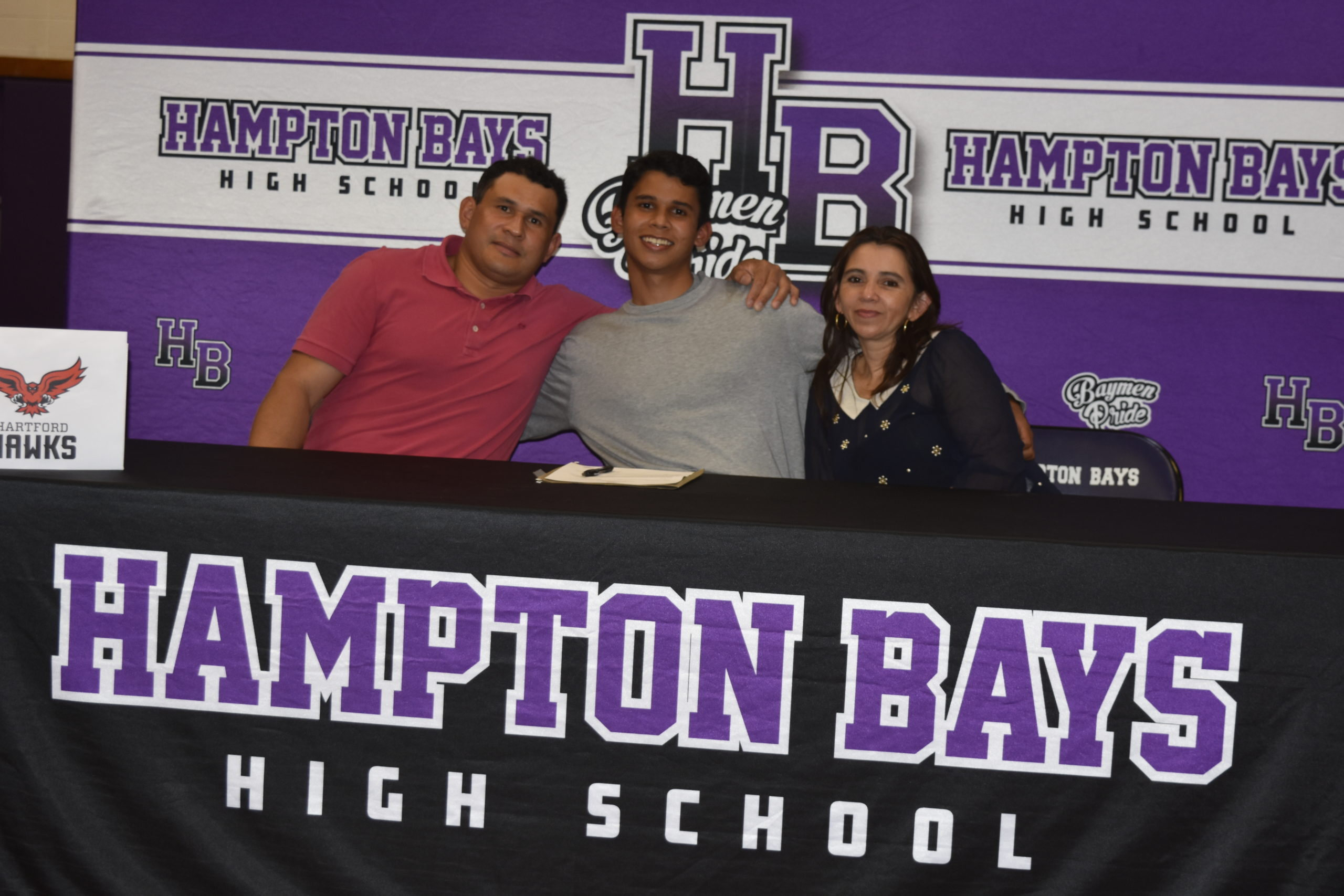 Darwin Fernandez, with his parents, Darwin and Cynthia Deras, after signing his letter of intent to run track at the University of Hartford.