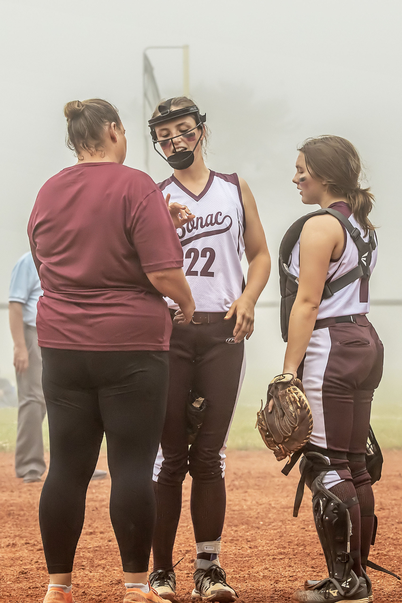 Caroline DiSunno has her pitching hand checked by her coach Annemarie Brownafter it was hit by a line drive.
