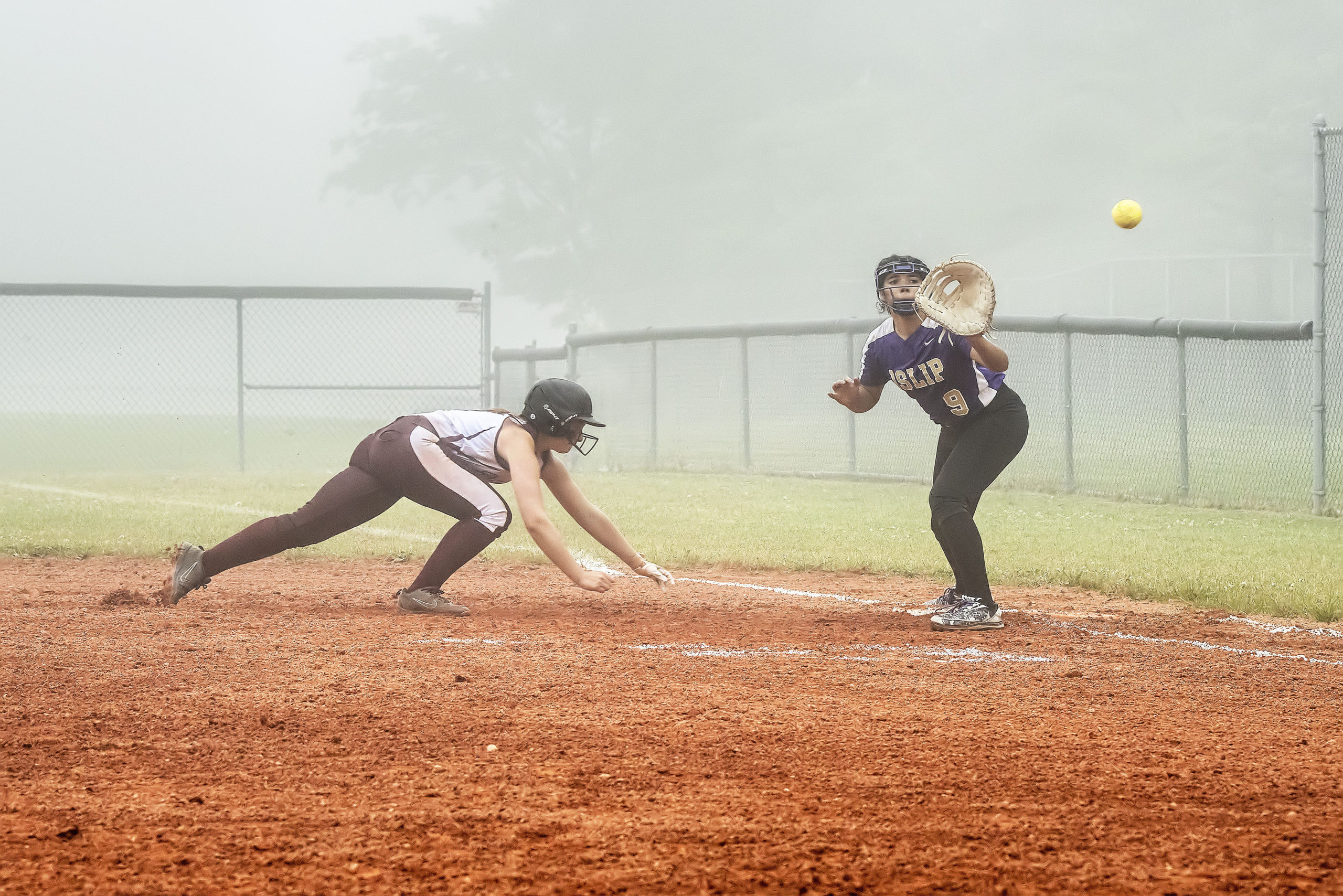 Junior Bonacker Leah Masi dives back to first base to avoid being picked off.