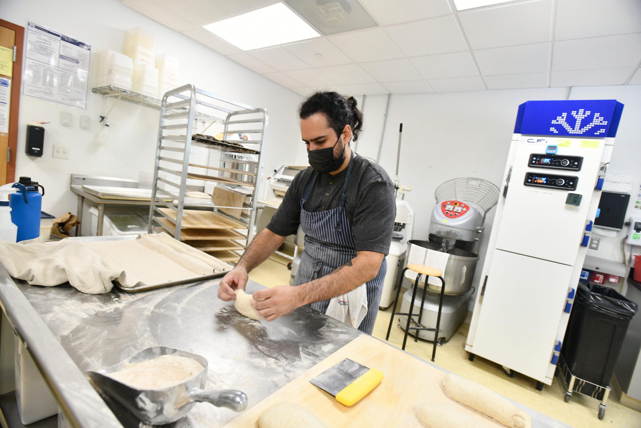 Chef Carlos Barbosa shapes loaves at the Newlight Breadworks kitchen in Calverton.  DANA SHAW