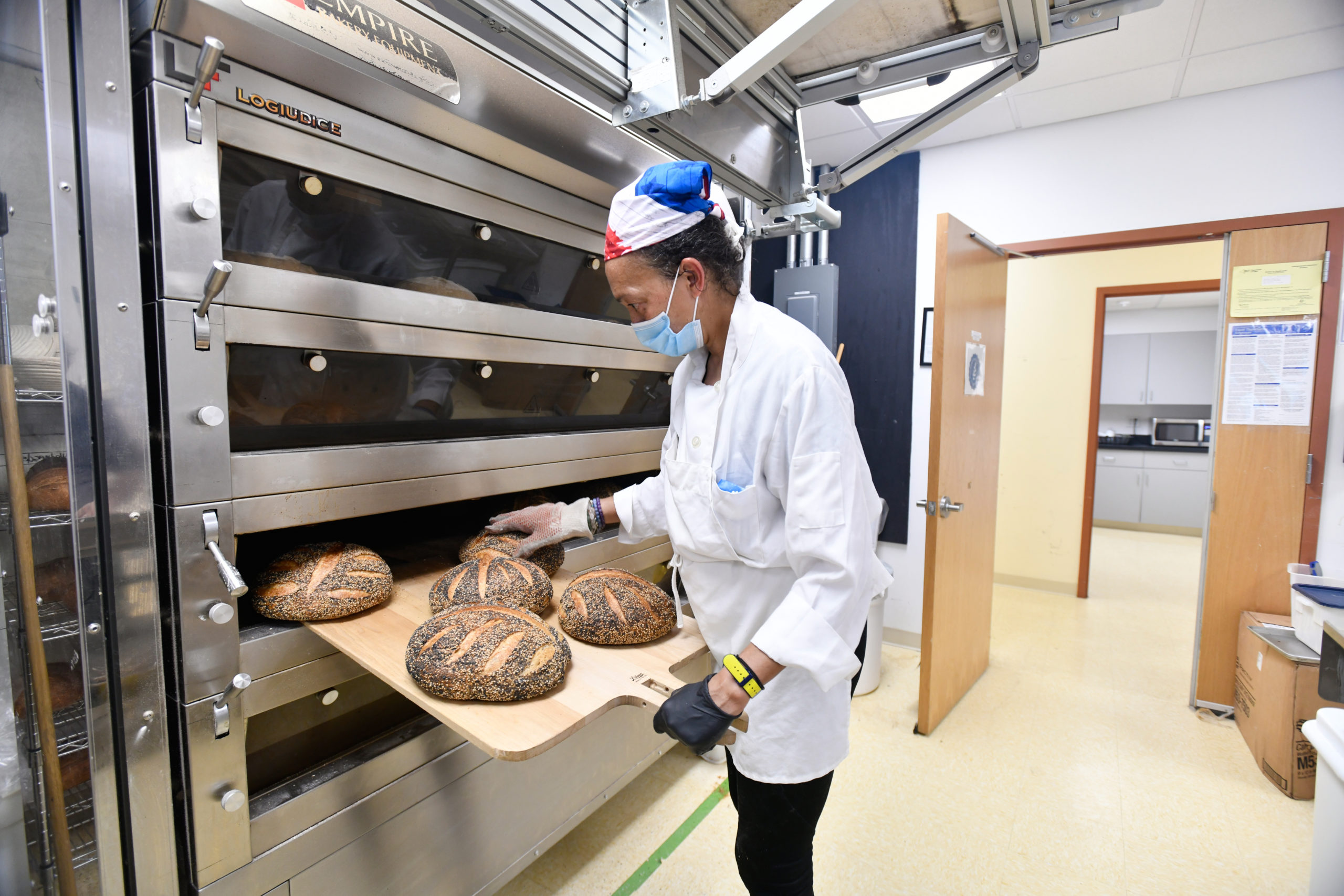 Baker Isabelle Saint-Marie pulls freshly baked loaves out of the oven.  DANA SHAW
