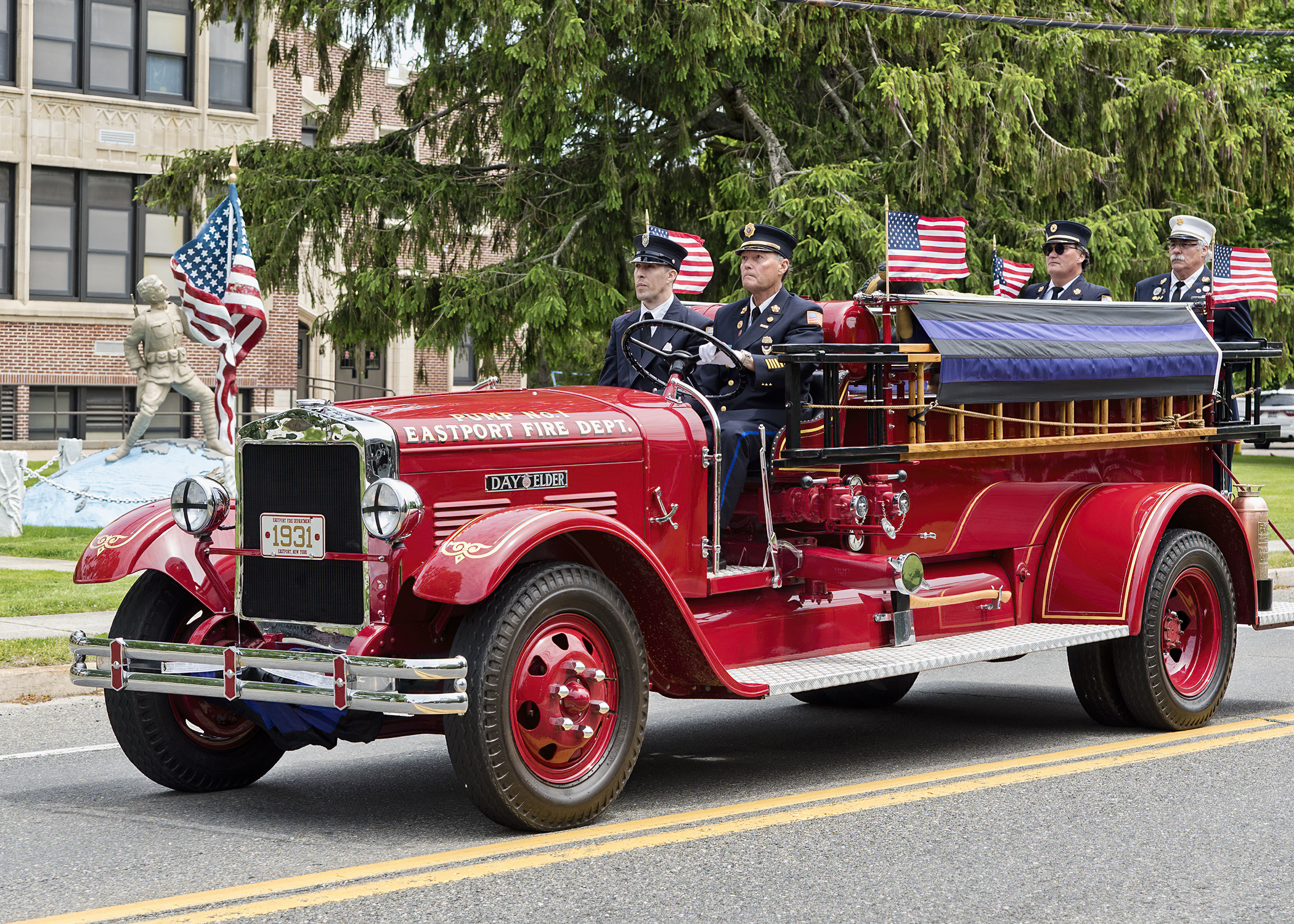 """The Eastport Fire Department's antique pumper carries the remains of Eastport Fire Department ex-chief and 65-year member James """"Jimmy"""" Baker past the Eastport Elementary School enroute to the cemetery last Wednesday morning."""