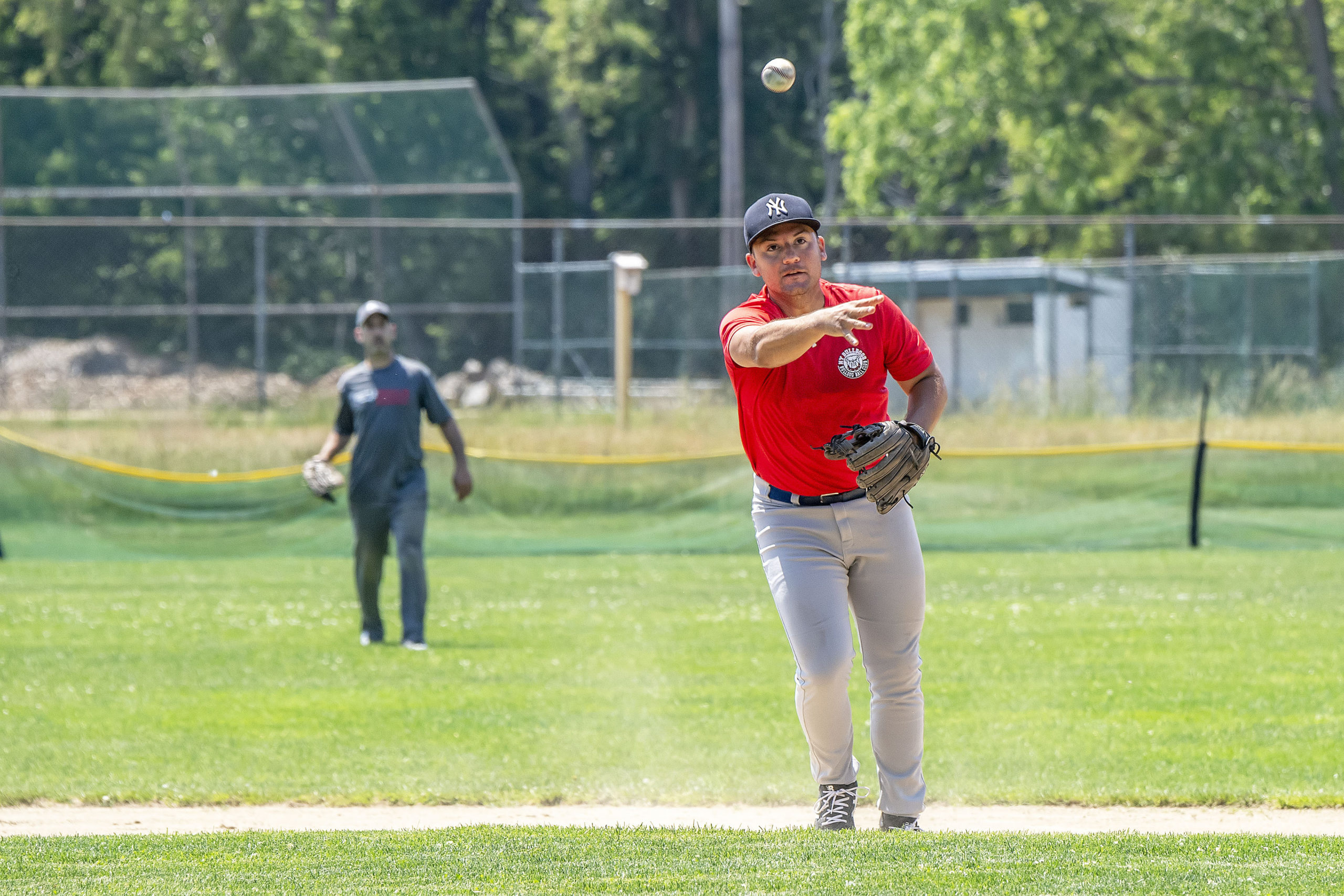 A Reds fielder throws to first base as the Hamptons Adult Hardball League South Fork Giants took on the New York Reds during the league's inaugural game at Mashashimuet Park in Sag Harbor on Sunday.