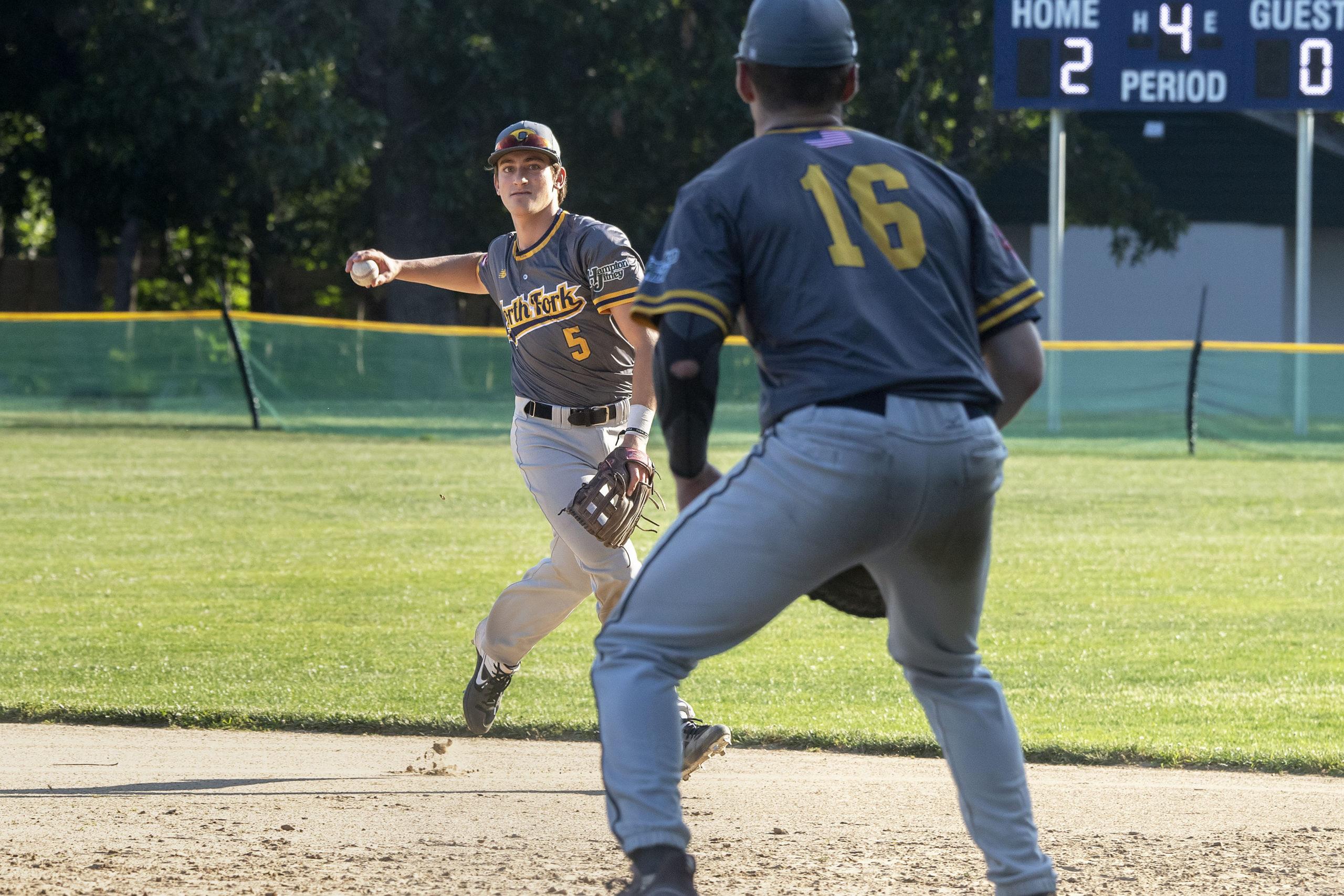 Osprey infielder Reece Rippoli throws to first baseman Steven Luttazi after fielding a grounder.