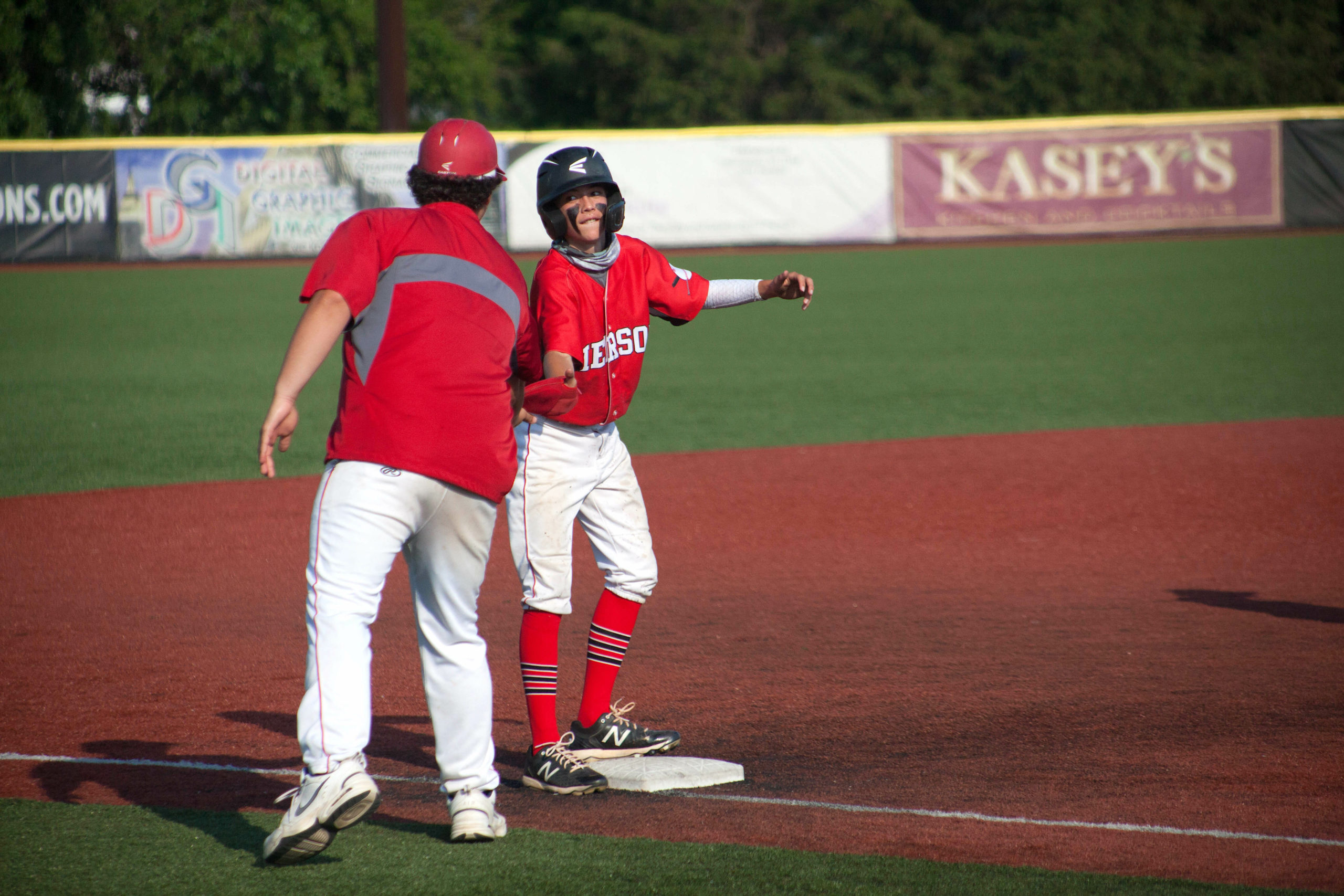 Pierson freshman Dominick Mancino high-fives coach Tyler LaBorne at third base for his offensive efforts.