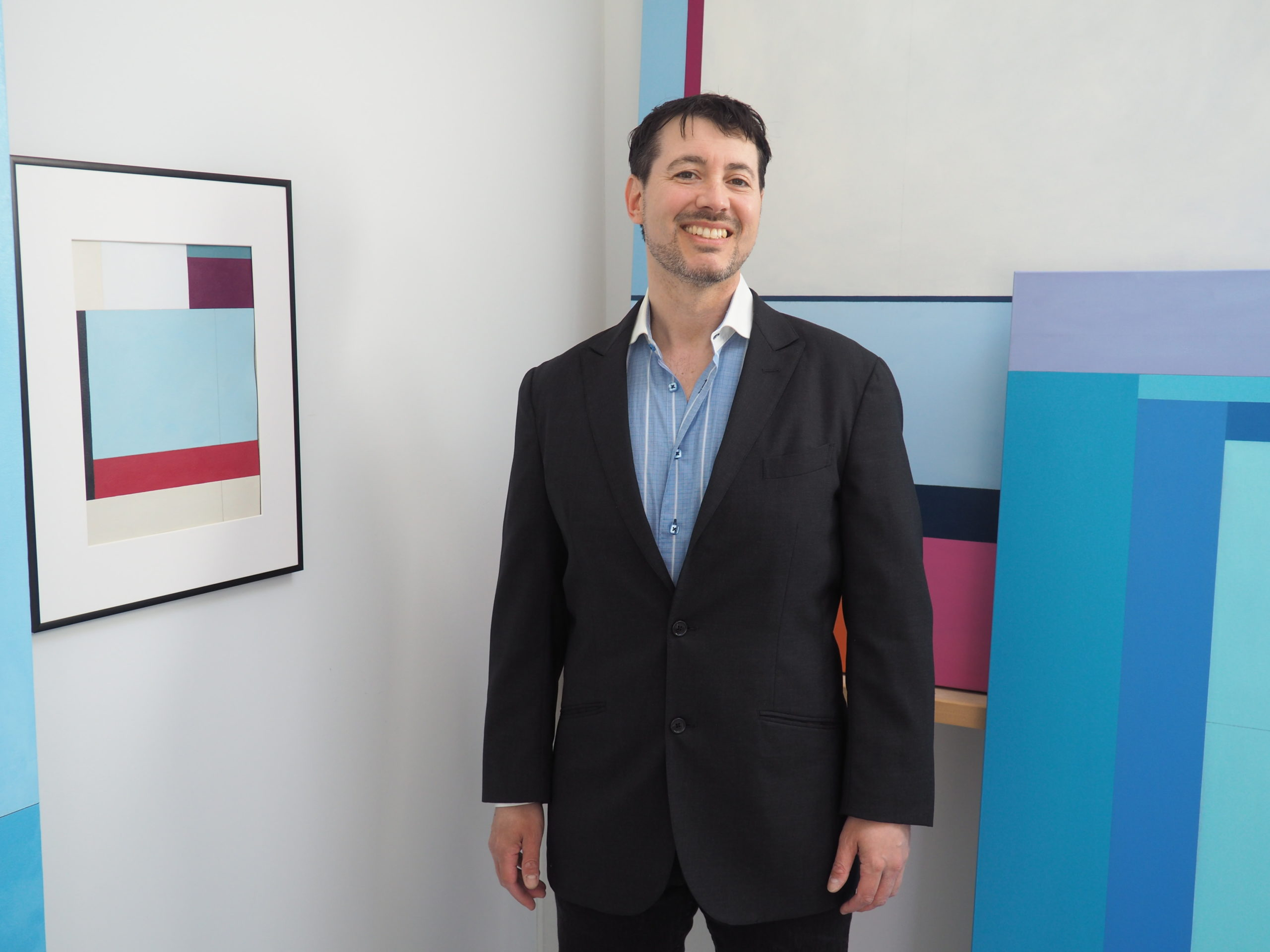Chris Kelly in his studio surrounded by his paintings.