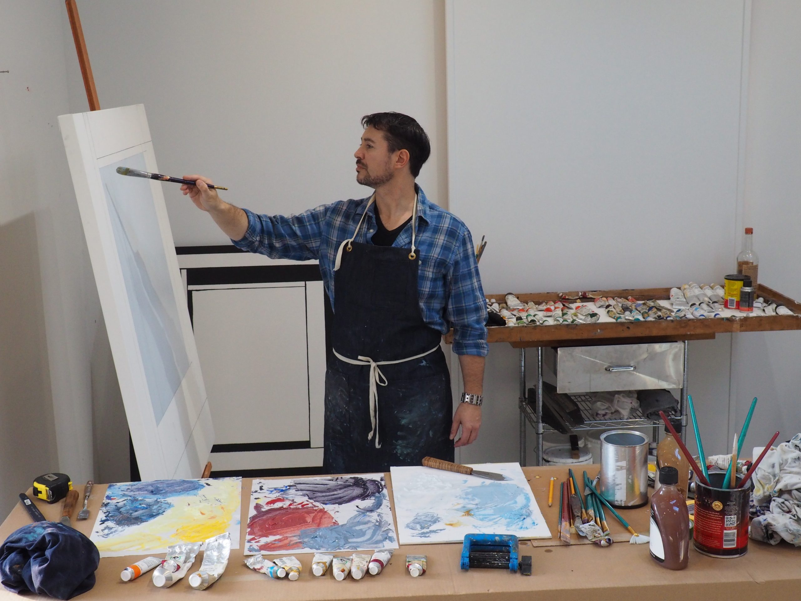 Artist Chris Kelly works on a painting in his studio.