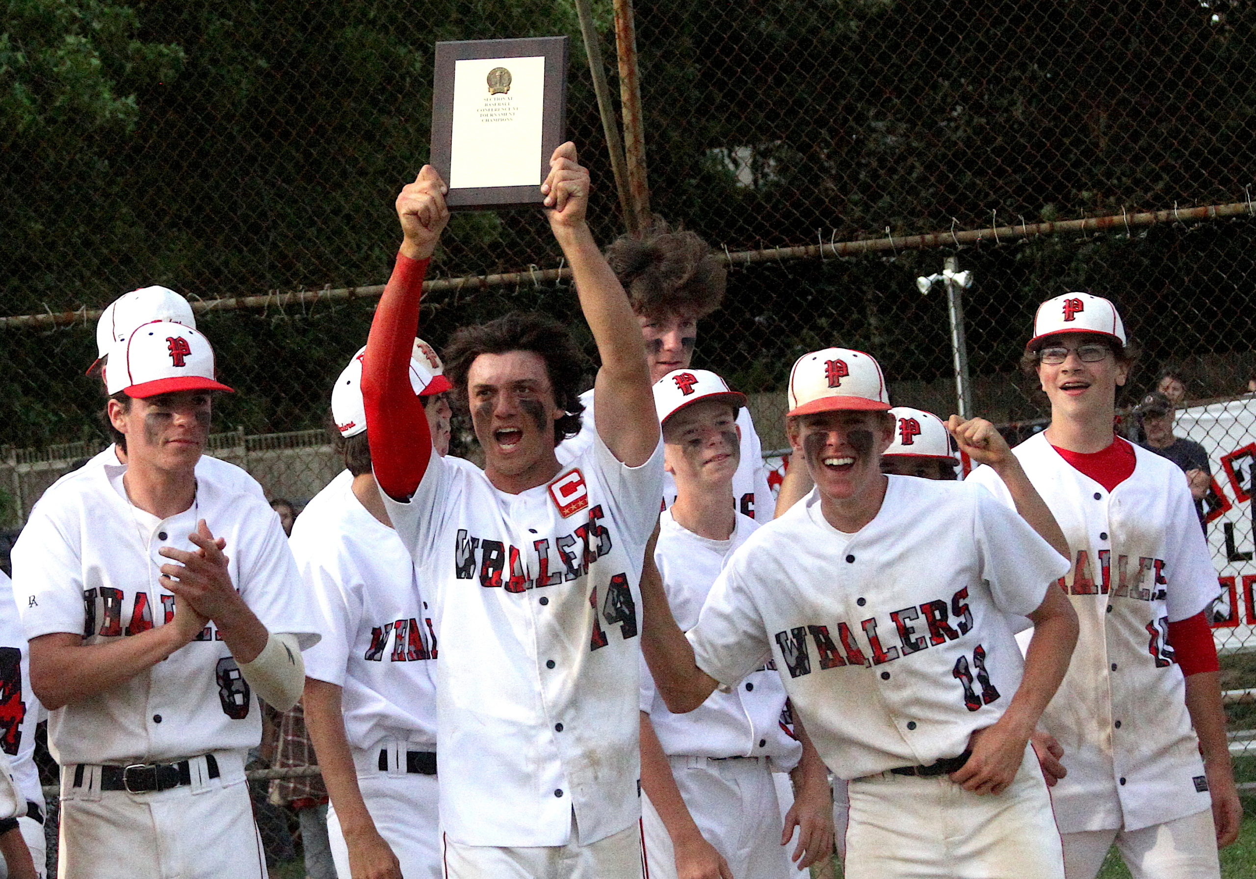 Senior Tucker Schiavoni hoists up Pierson's Suffolk County championship plaque. DESIRÉE KEEGAN