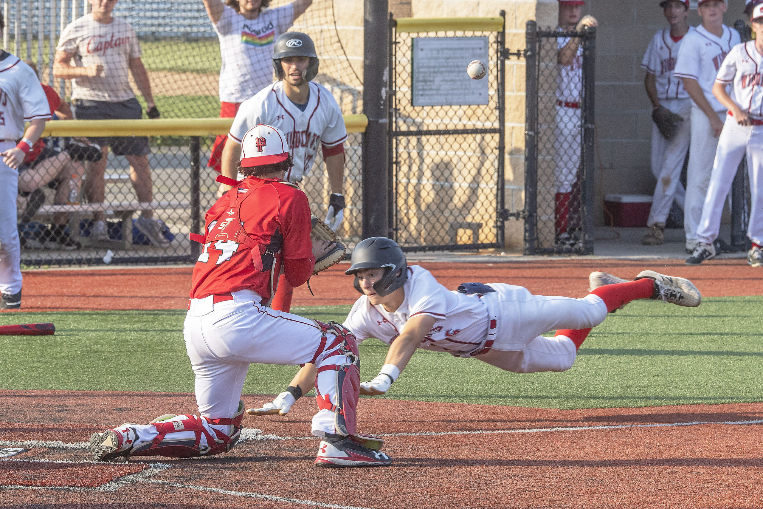 A Wheatley runner dives for home as the ball caroms off Pierson catcher Tucker Schiavoni's glove.