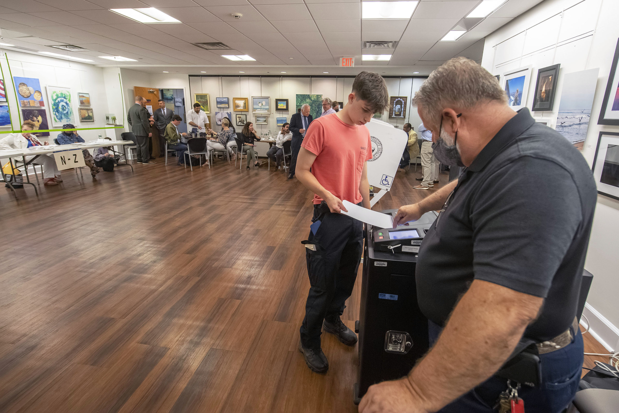 An election official helps a young voter insert his ballot into the voting machine during the 2021 Southampton Village Mayoral election at the Southampton Cultural Center on Friday night. MICHAEL HELLER